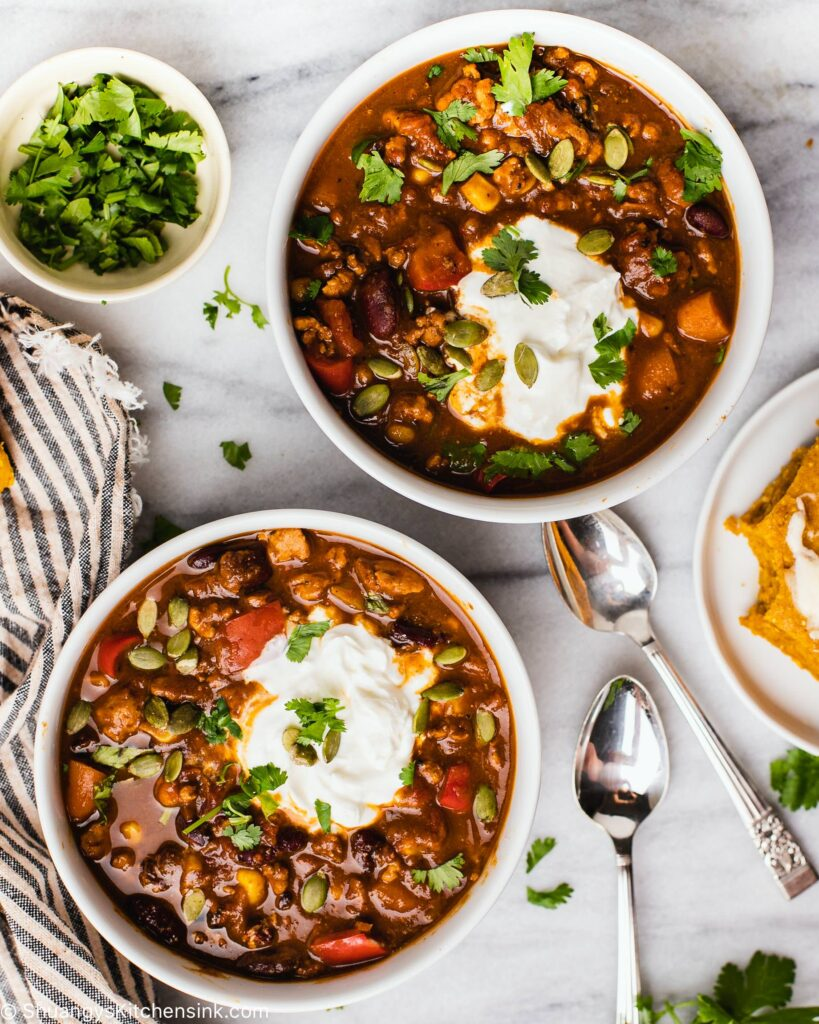 Two bowls with pumpkin turkey chili topped with dairy-free sour cream and cilantro