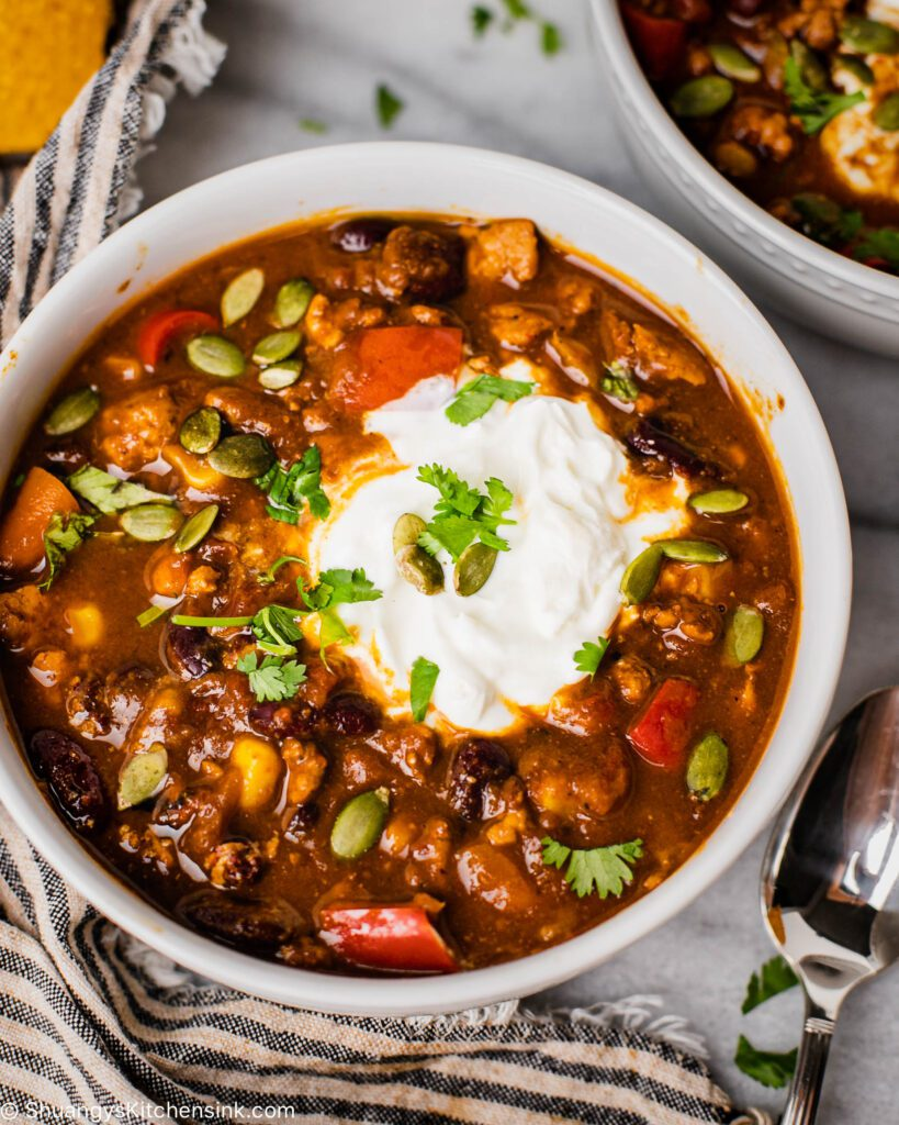 A bowl of instant pot turkey chili topped with dairy-free sour cream and cilantro