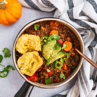 A serving pot with creamy pumpkin turkey chili. Topped with avocado, cilantro, avocado and one corn bread muffin split in half.