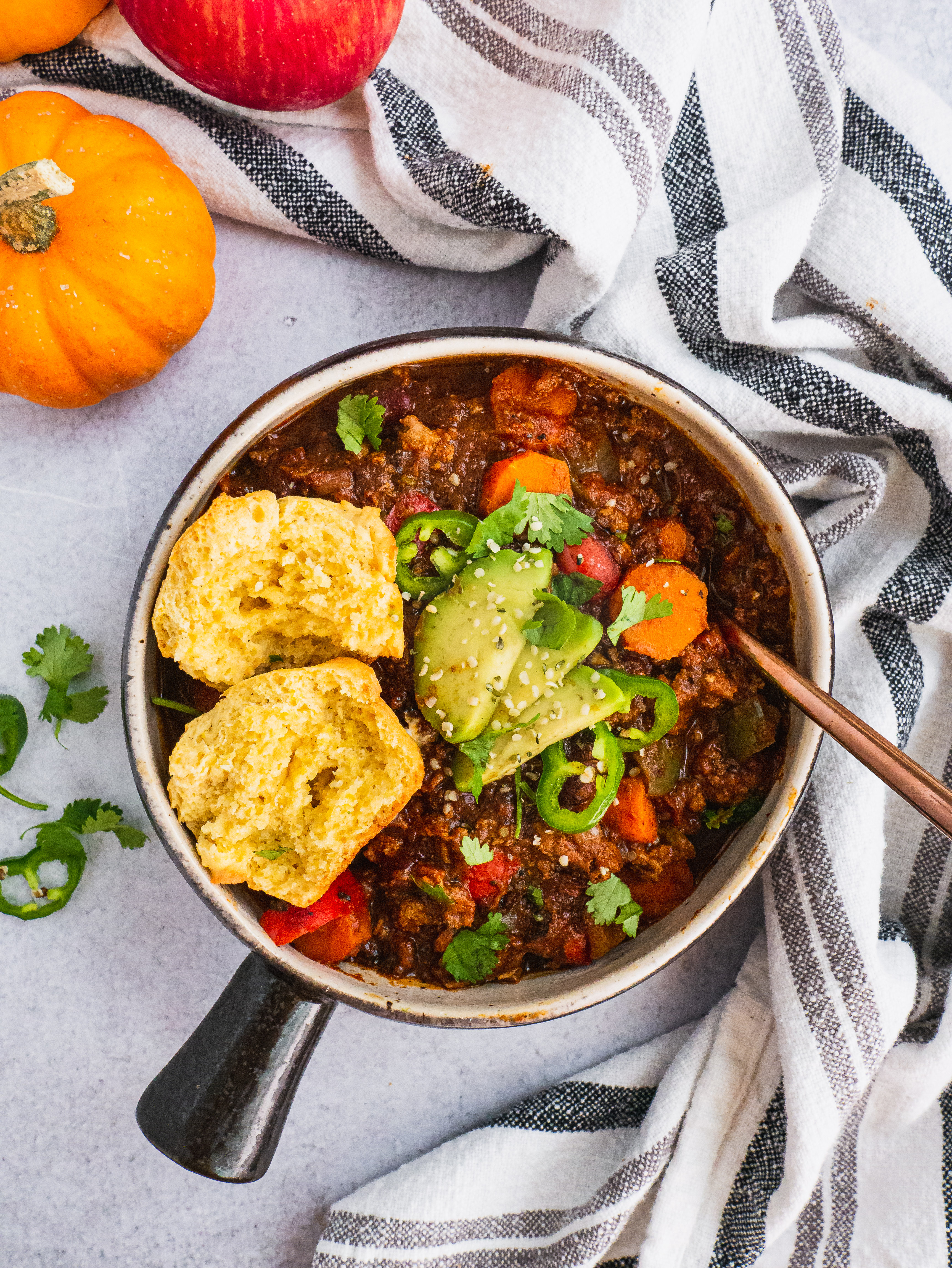 A serving pot with creamy pumpkin turkey chili. Topped with avocado, cilantro, avocado and one corn bread muffin split in half.