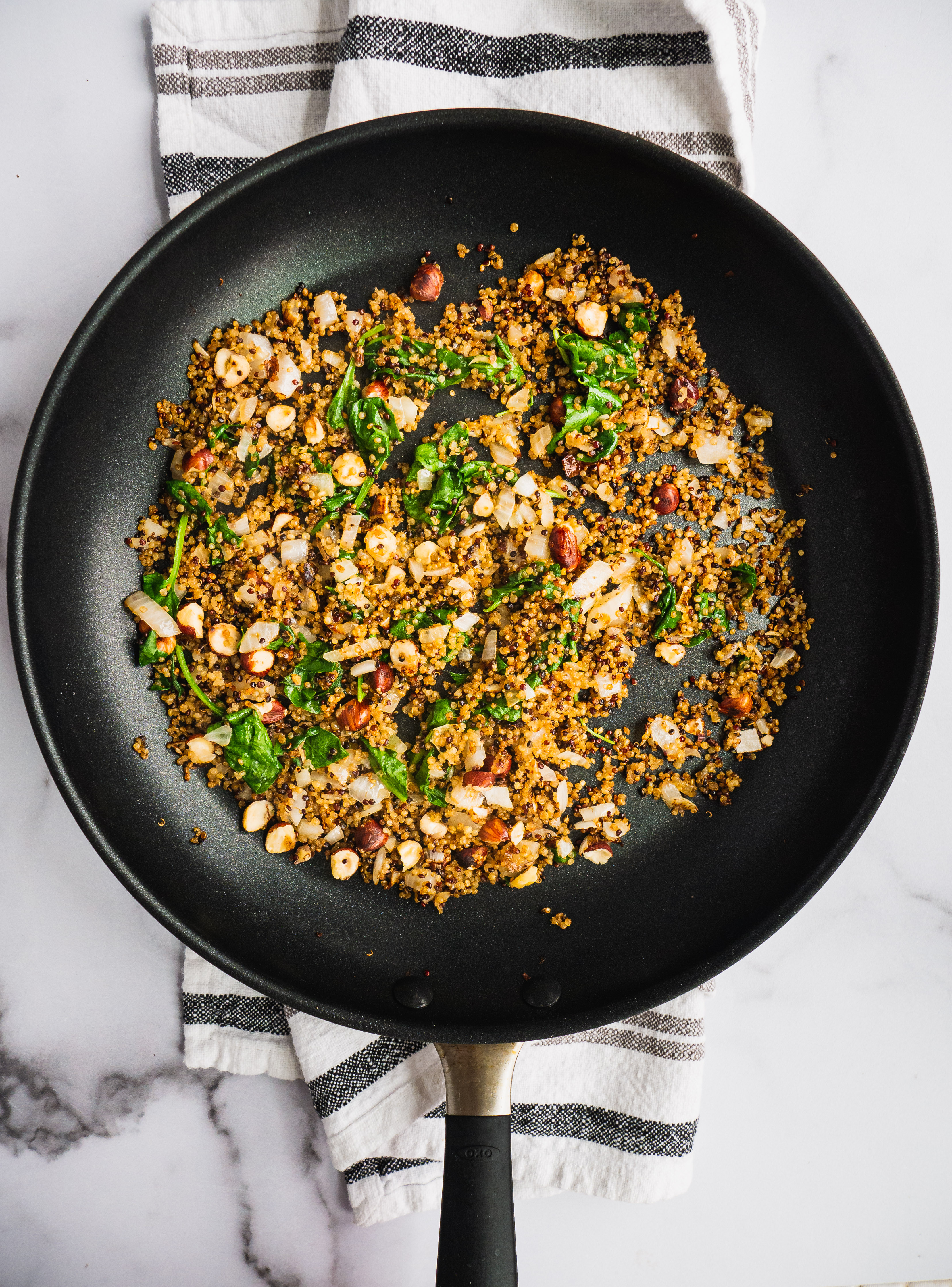 A sauteing pan with quinoa, spinach, hazelnuts, and onion.