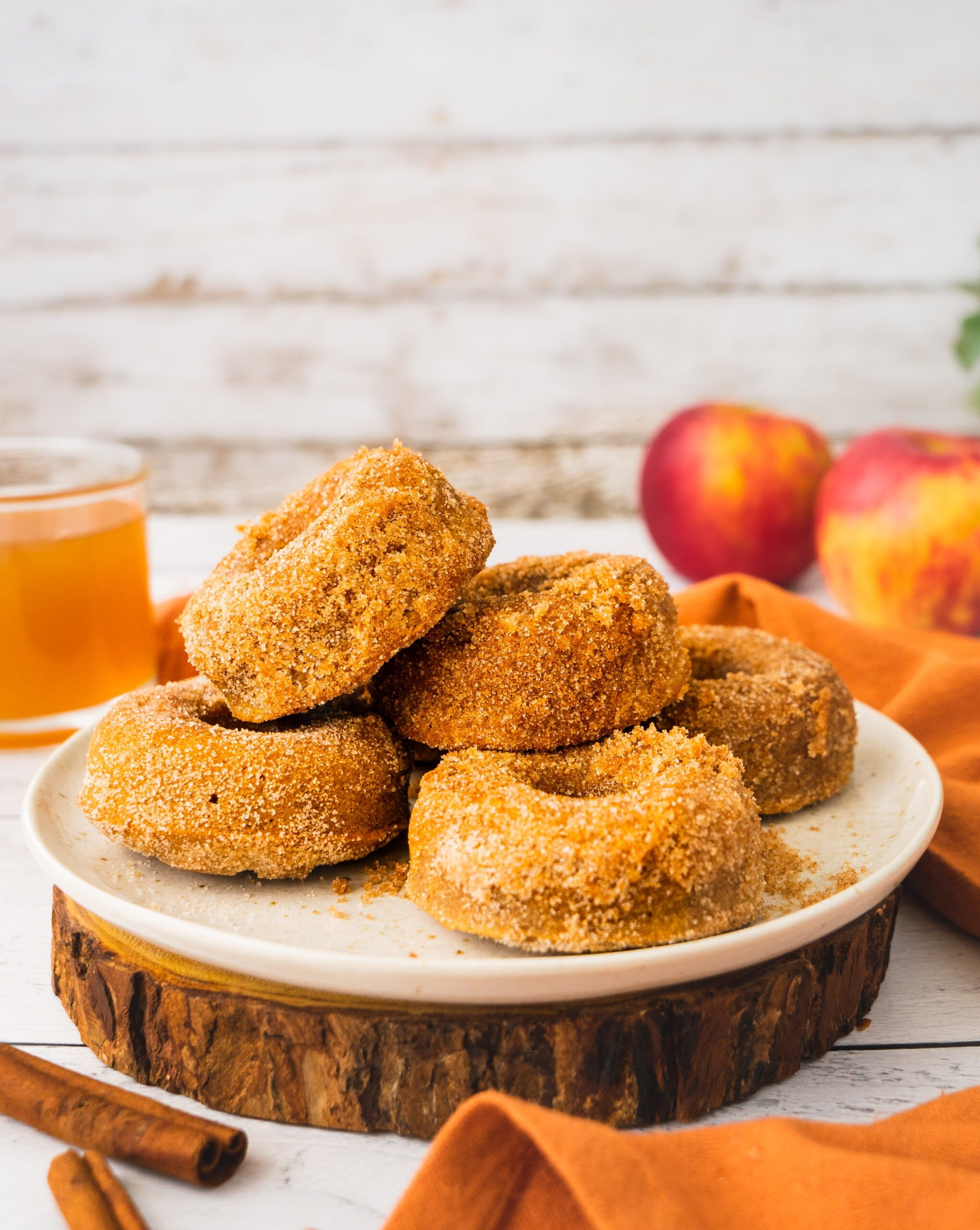 A plate of sweet baked apple cider donuts coated i cinnamon sugar. There is a bite in one of the donuts and a glass of hot apple cider in the back.