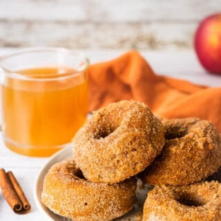 a plate of paleo healthy fluffy apple cider donuts. There is a glass of warm cider and an apple in the background. There are two pieces of cinnamon sticks in the foreground. My hand is reaching to grab one of the donuts.