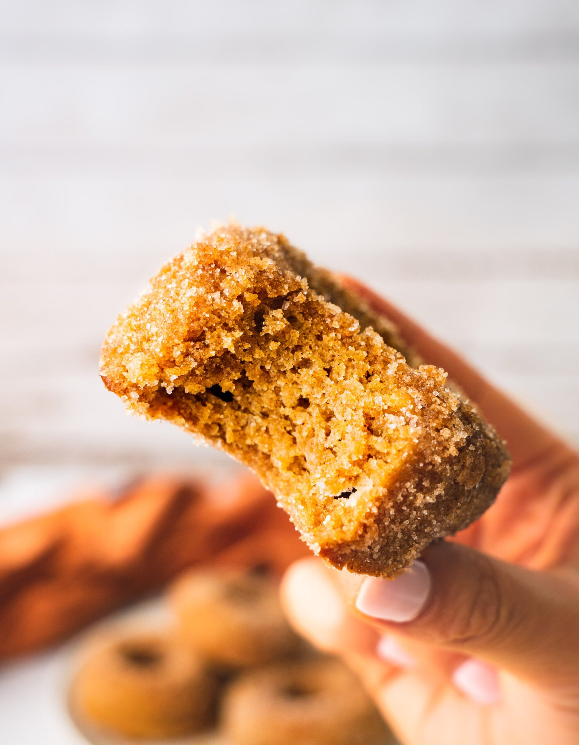 A piece of fluffy and airy apple cider donuts coated i cinnamon sugar. There is a bite in one of the apple cider donuts and a glass of hot apple cider in the back.