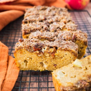 A loaf of healthy crumble bread with crumble toppings on a drying wrack. With an apple and pumpkin the background.