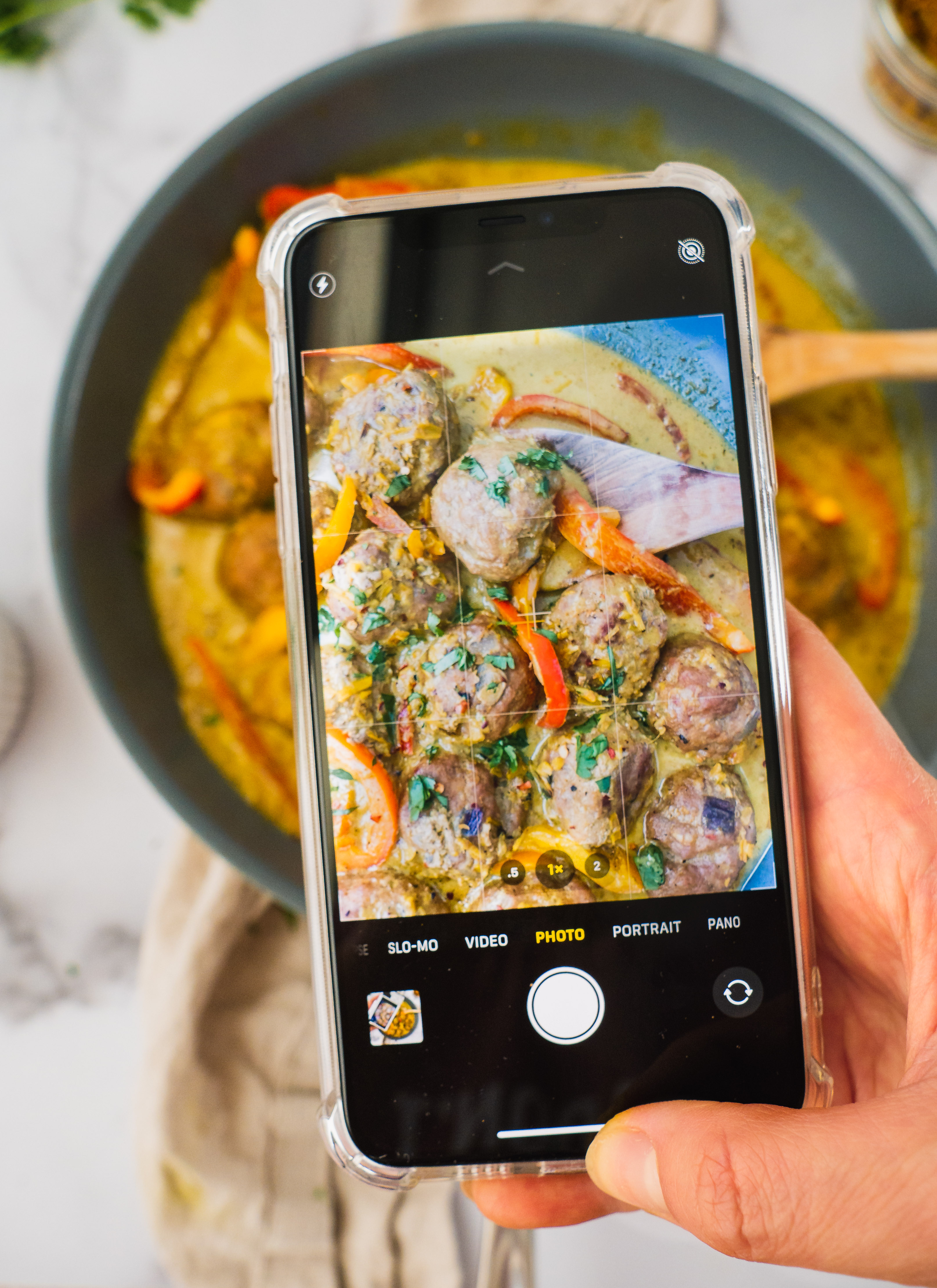 In a blue sauce pan, there are the cooked yellow thai coconut curry meatballs with fresh cilantro on top. There is a wooden spoon in the coconut curry soup as well. an Iphone is shooting this scene. for instagram