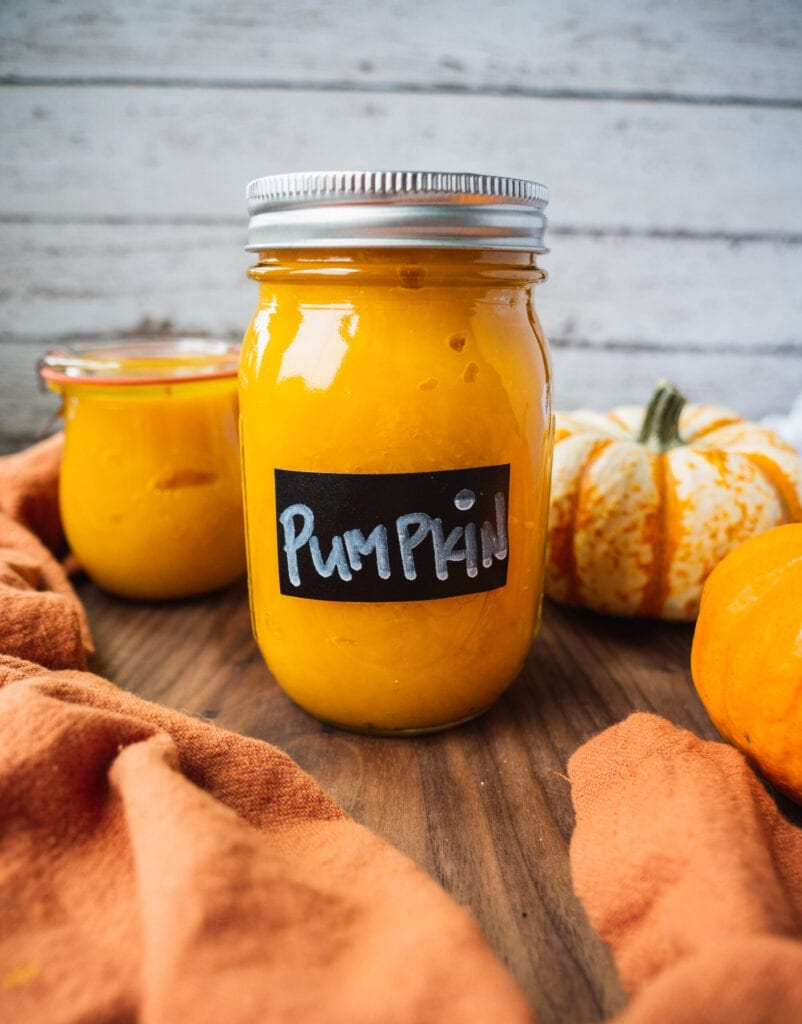 a jar of fresh homemade pumpkin puree from scratch. There is a pumpkin in the background.