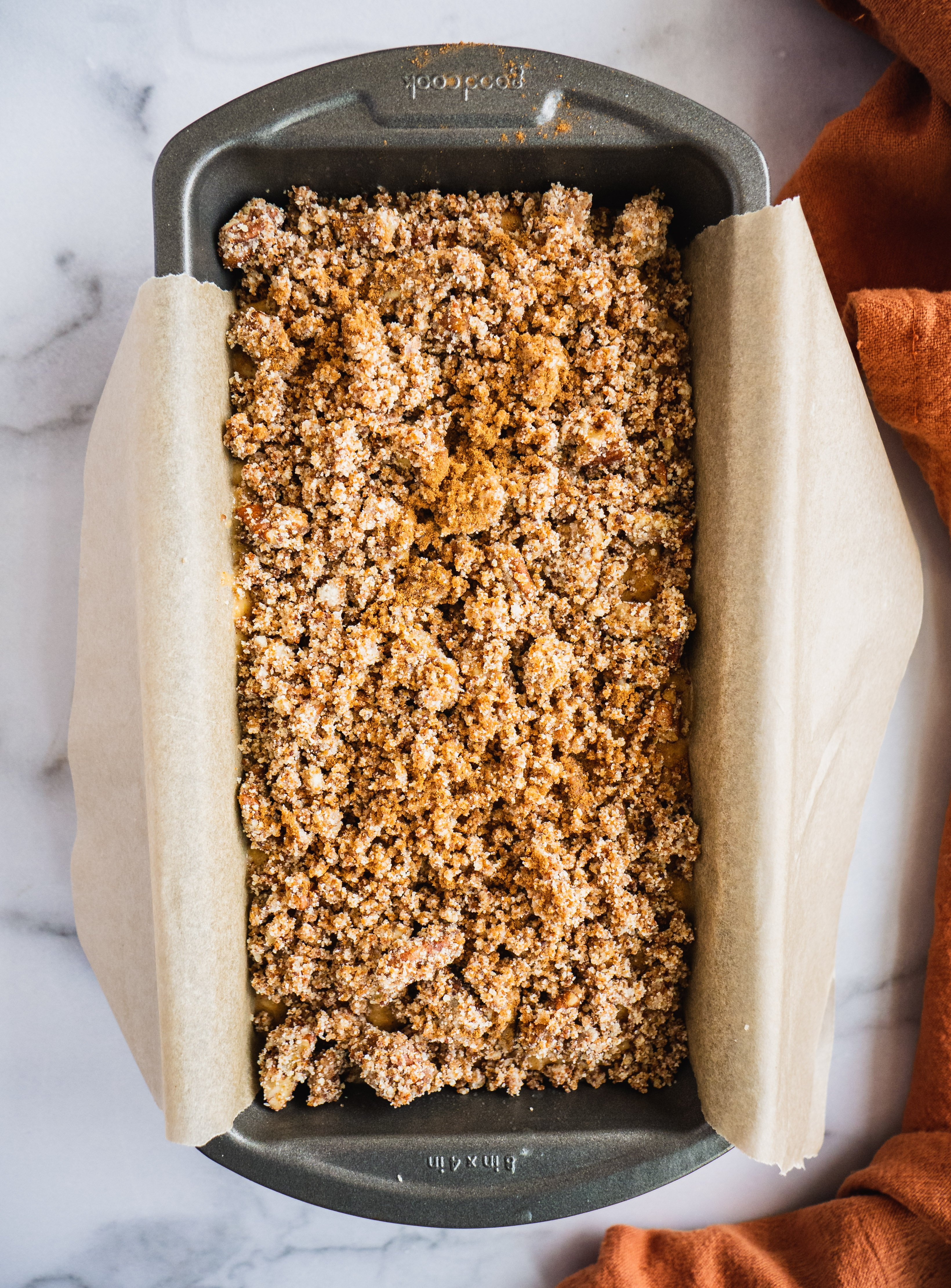 A loaf of apple bread with crumble toppings in a loaf pan