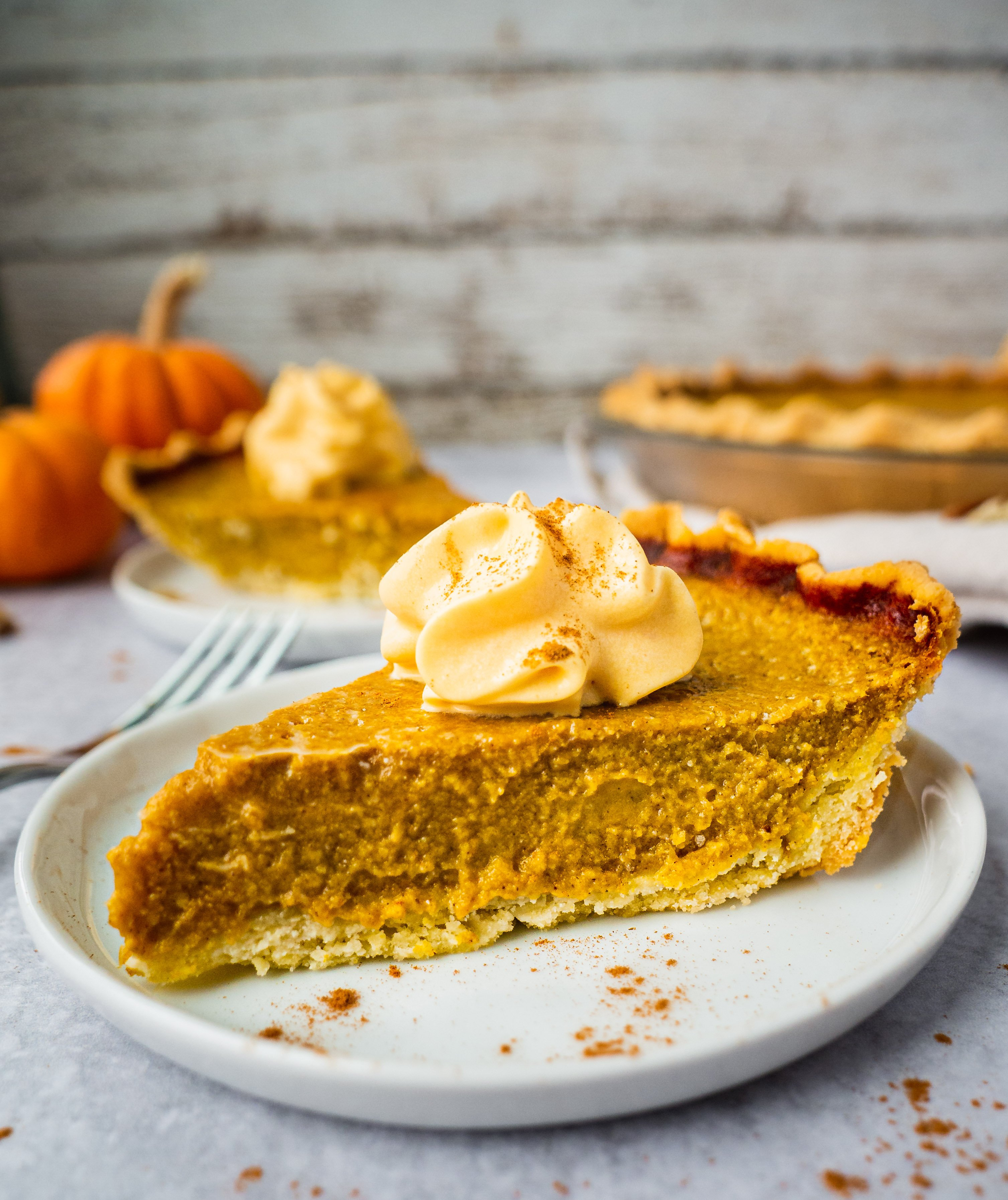 a piece of homemade pumpkin pie made with sweet, buttery and flaky gluten free pie crust.