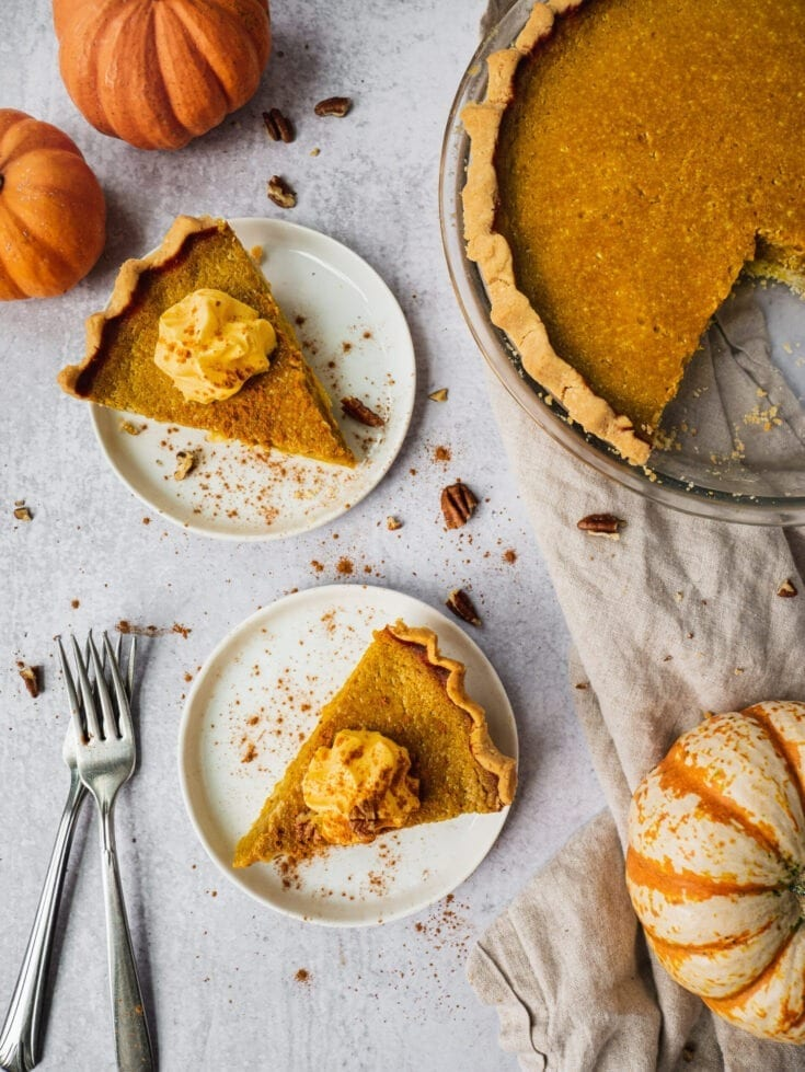 On a table there is a healthy pumpkin pie being sliced to serve. There are 3 little pumpkins around the pie. Two slices of pumpkin pies are placed on little plates, topped with whipped cream and pumpkin spice. There are two forks on the side.