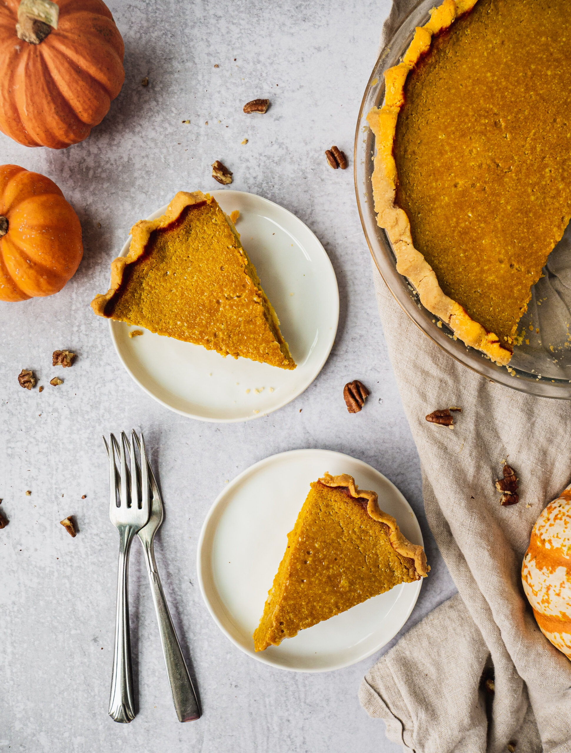 On a table there is a healthy pumpkin pie being sliced to serve. There are 3 little pumpkins around the pie. Two slices of pumpkin pies are placed on little plates, topped with whipped cream and pumpkin spice. There are two forks on the side. Pecans are sprinkled over the table