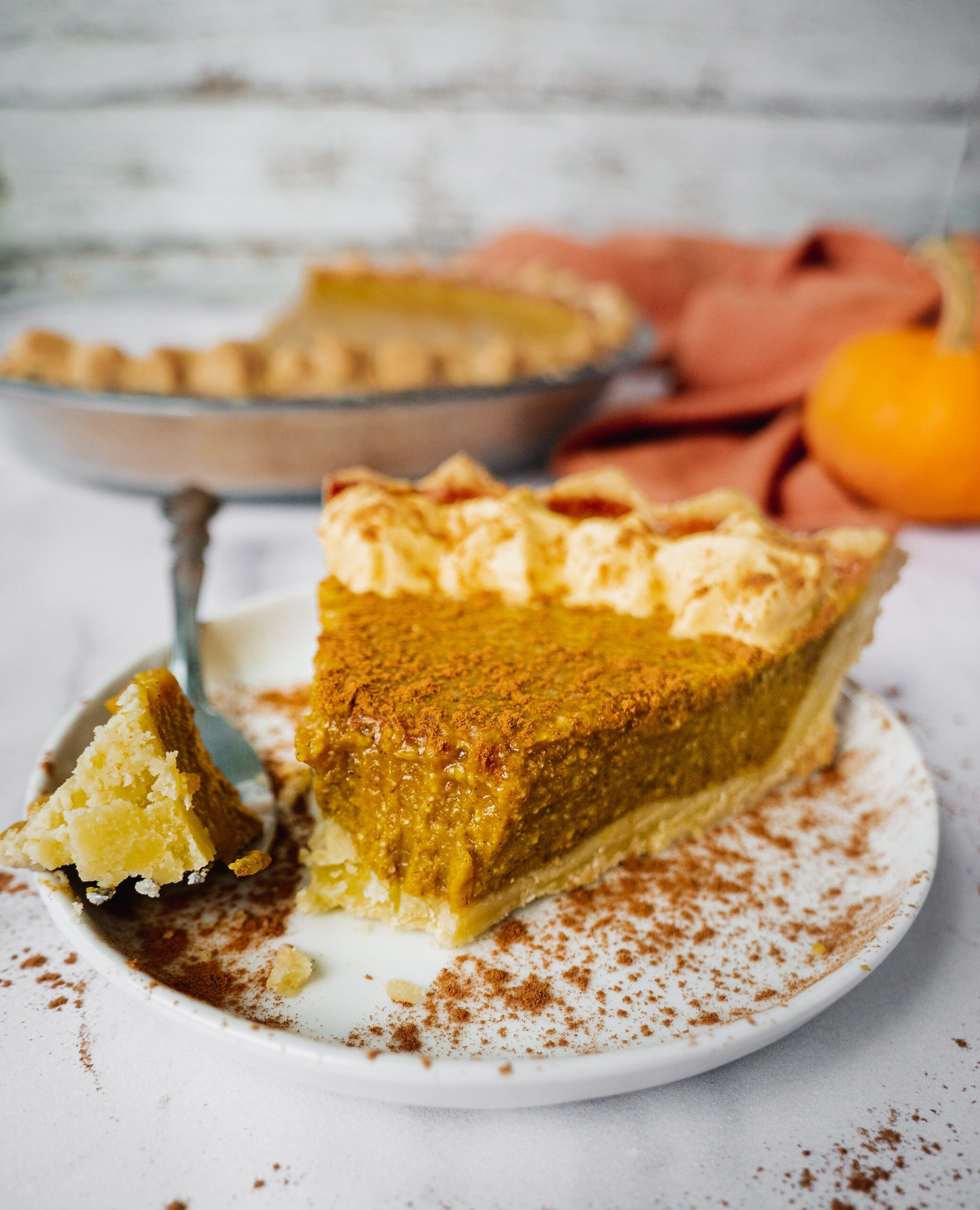 A slice of pumpkin pie on a serving plate with whipped cream on top and pumpkin spice. There is the rest of the pie in the background.