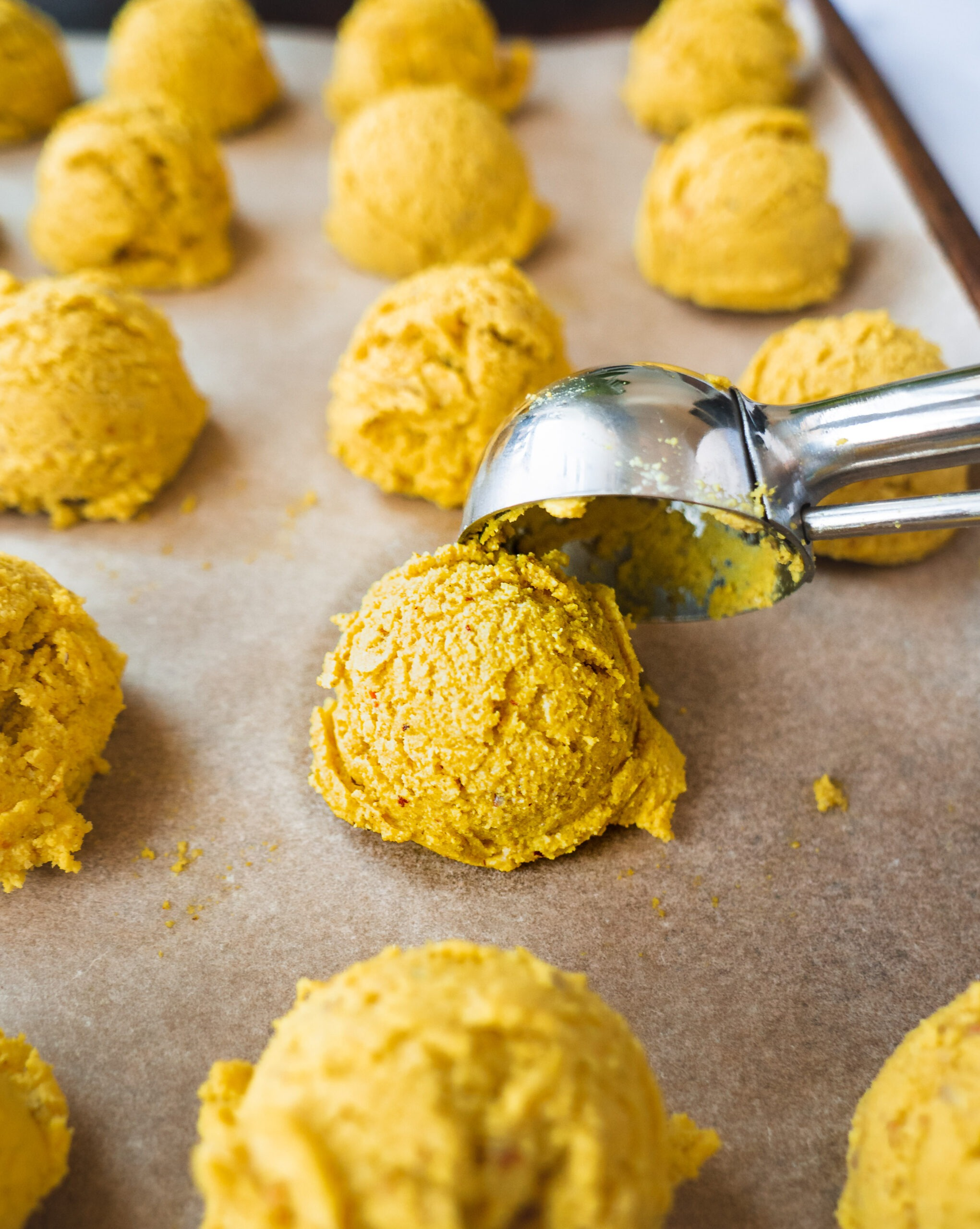 a cookie scoop is used to make yellow cookie dough-like balls