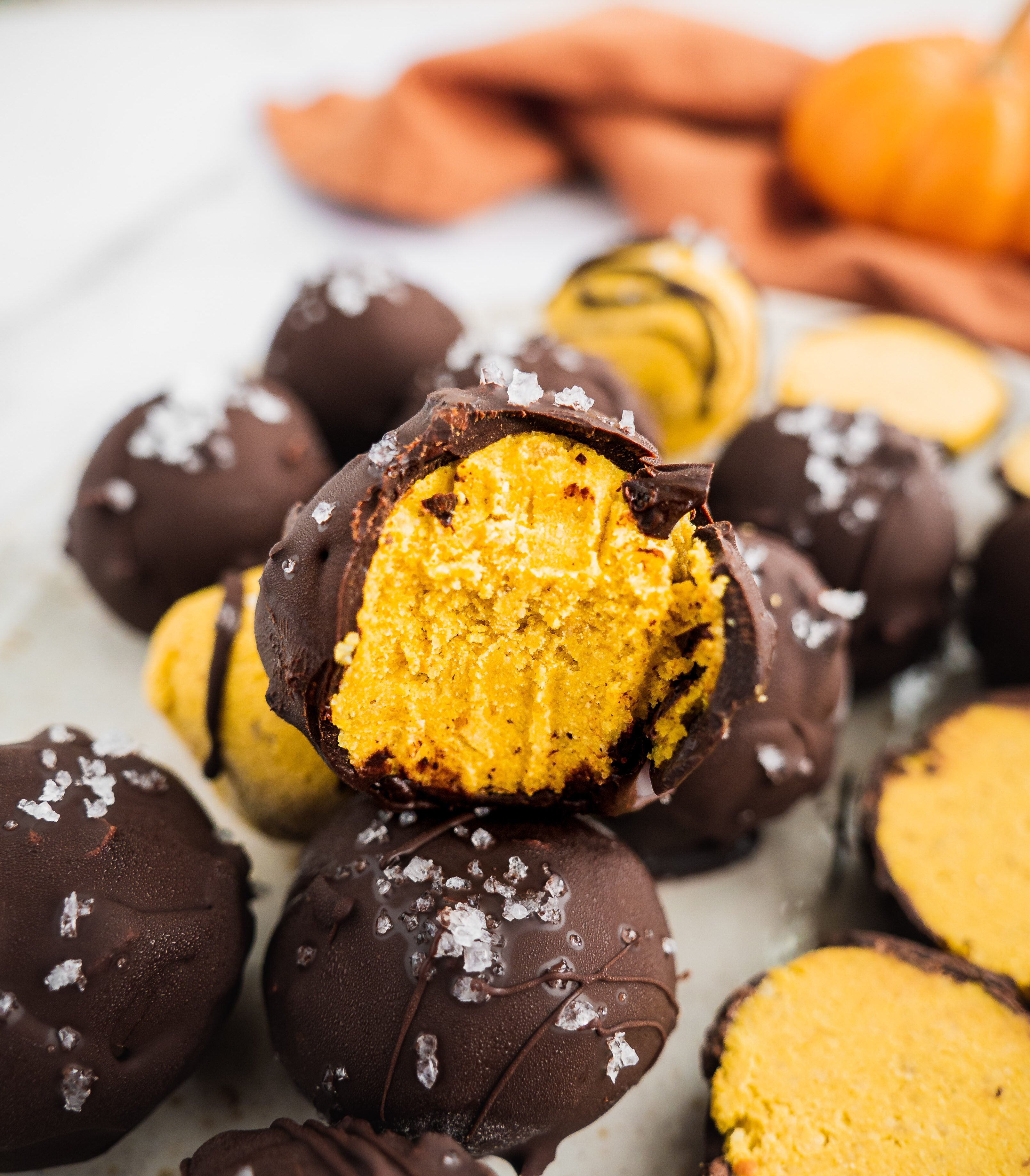 A piece of pumpkin spice chocolate truffle with a bite in the middle. There is a orange kitchen towel in the background.