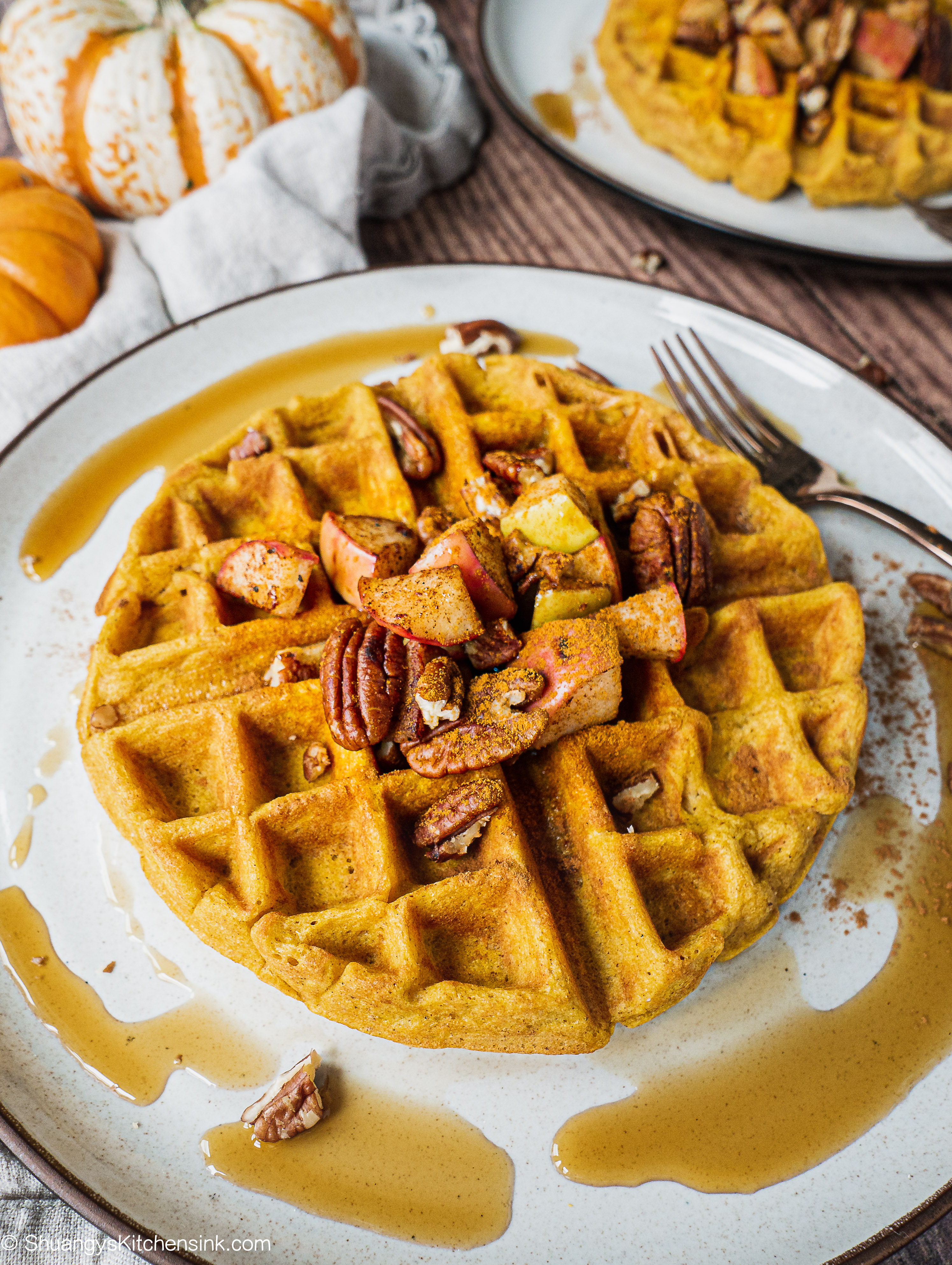 A paleo pumpkin waffle topped with sautéed apples and spiced pecans. Also drizzle of maple syrup. There is another waffle in the background and a little pumpkin on the kitchen towel.