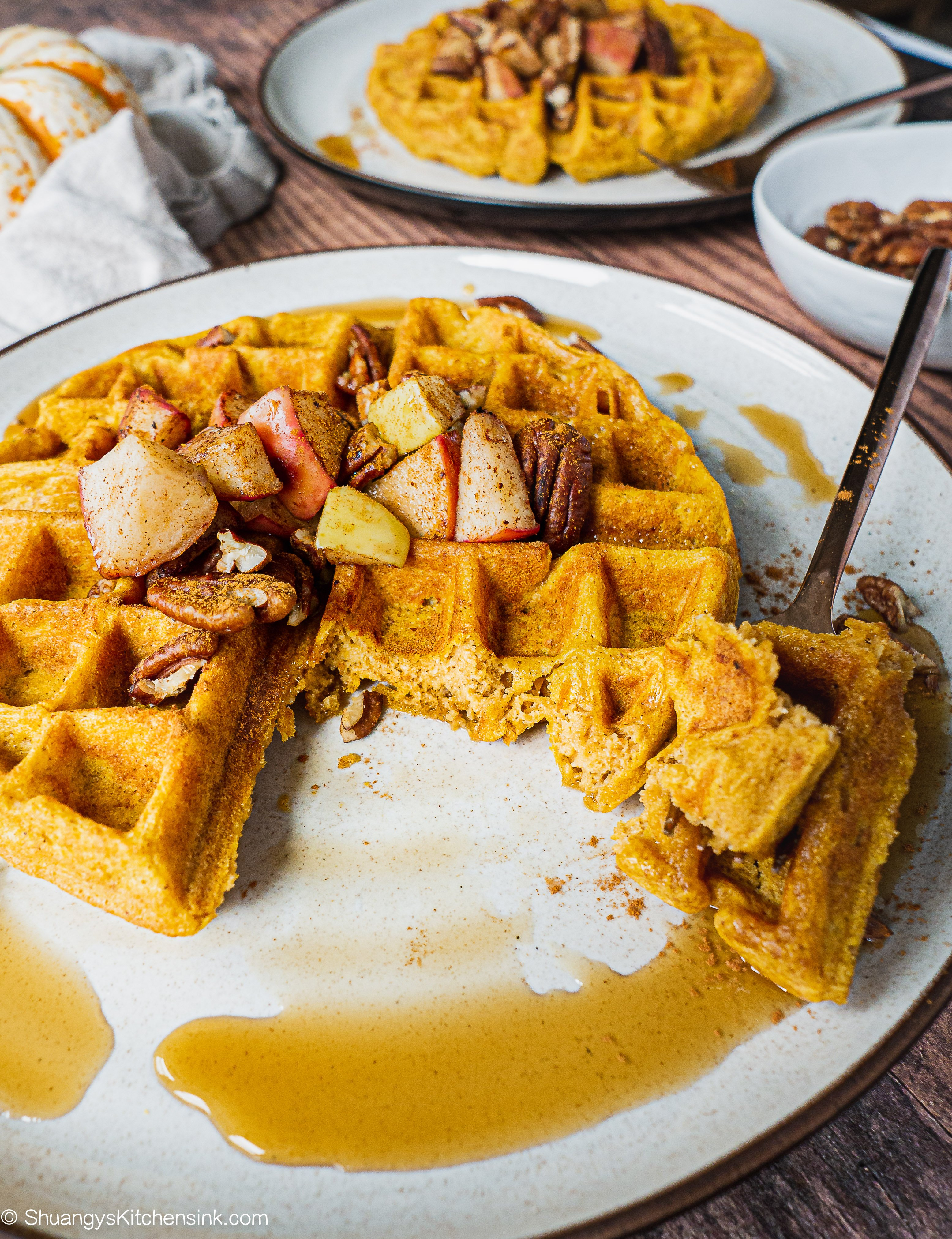 A paleo pumpkin waffle topped with sautéed apples and spiced pecans. Also drizzle of maple syrup. There is another waffle in the background and a little pumpkin on the kitchen towel. A fork has taken a bite off of the waffle. the texutre inside looks fluffy.