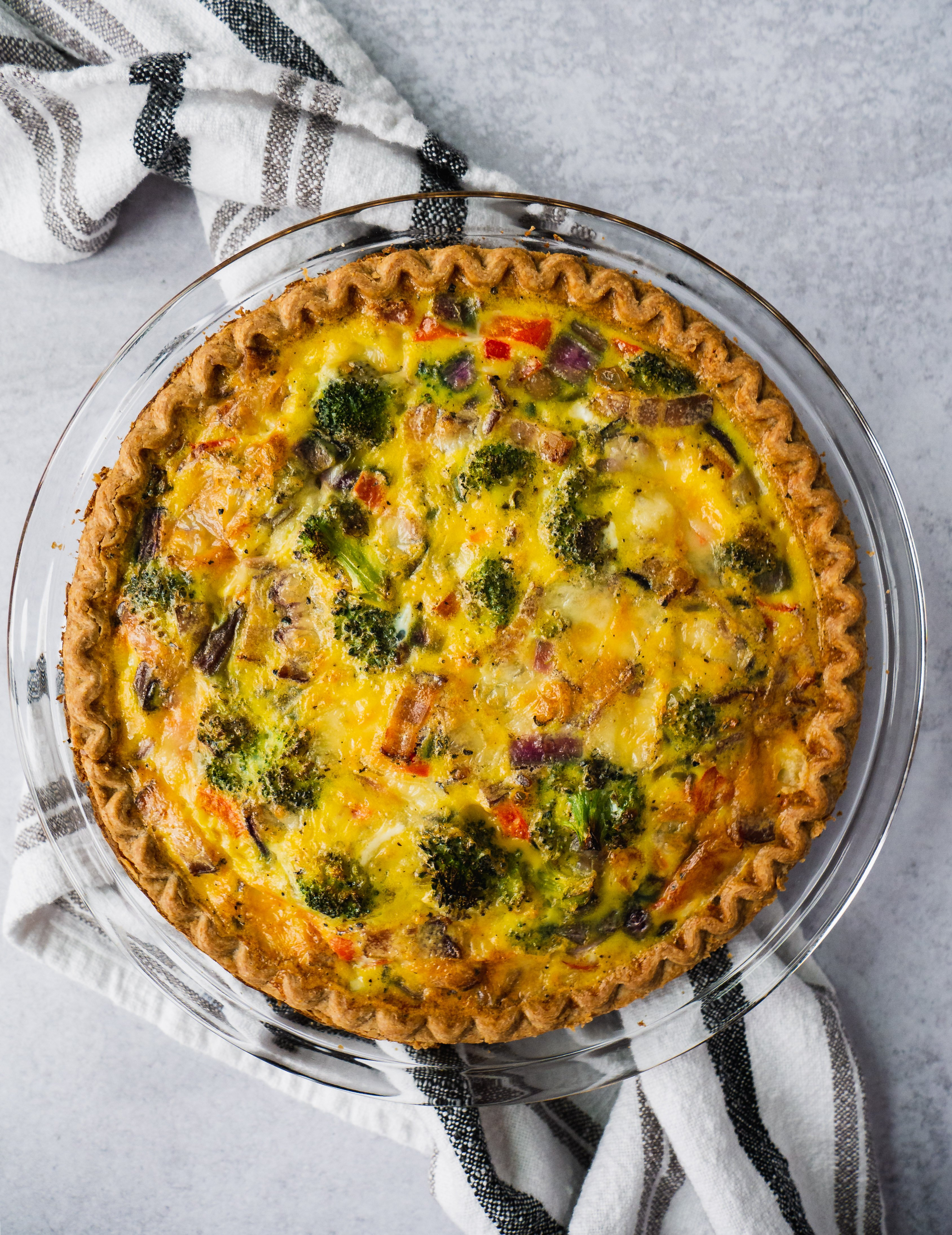 A broccoli quiche with bacon fresh out of the oven sitting on top of a dish towel.