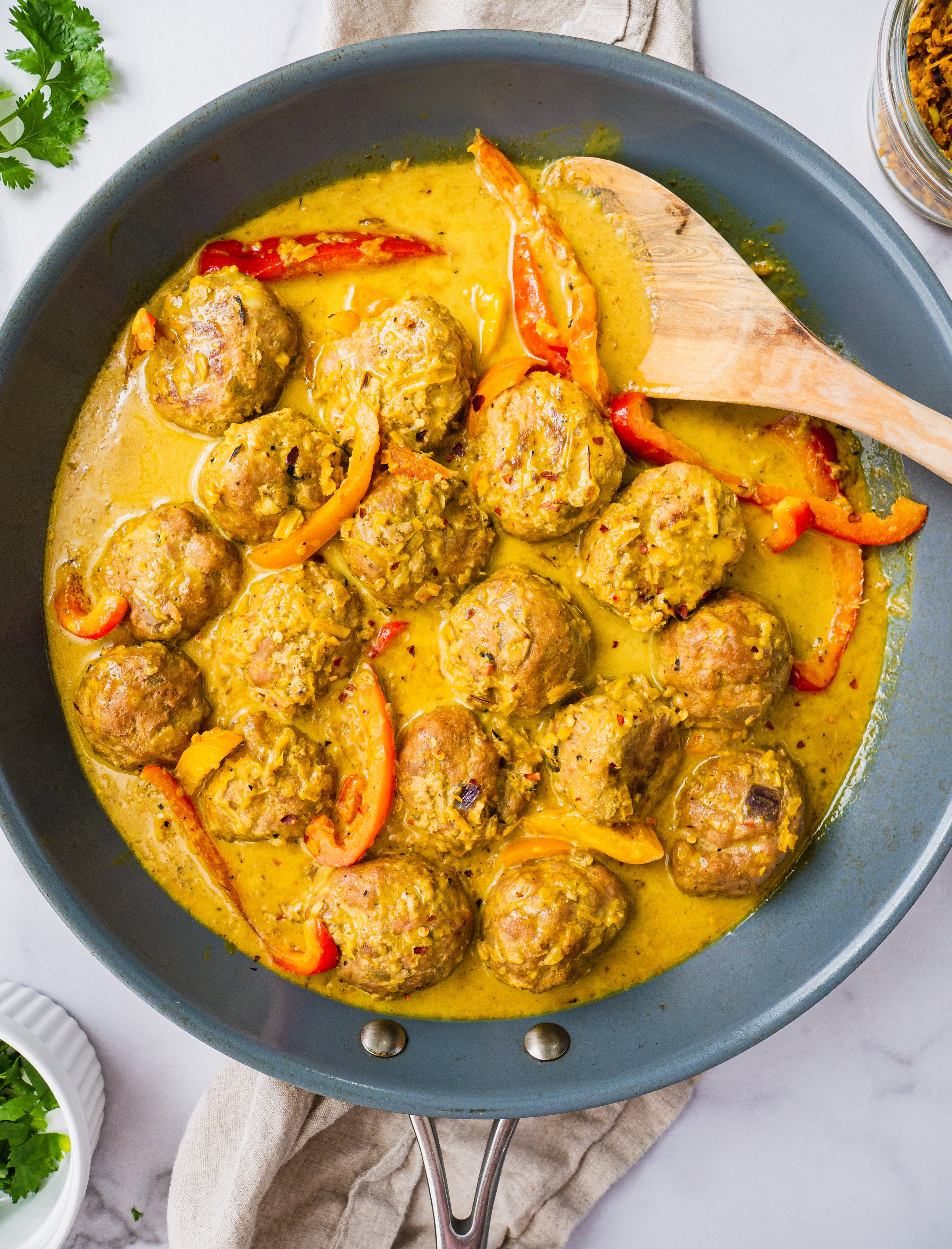 In a blue sauce pan, there are the cooked yellow thai coconut curry meatballs with fresh cilantro on top. There is a wooden spoon in the coconut curry soup as well.