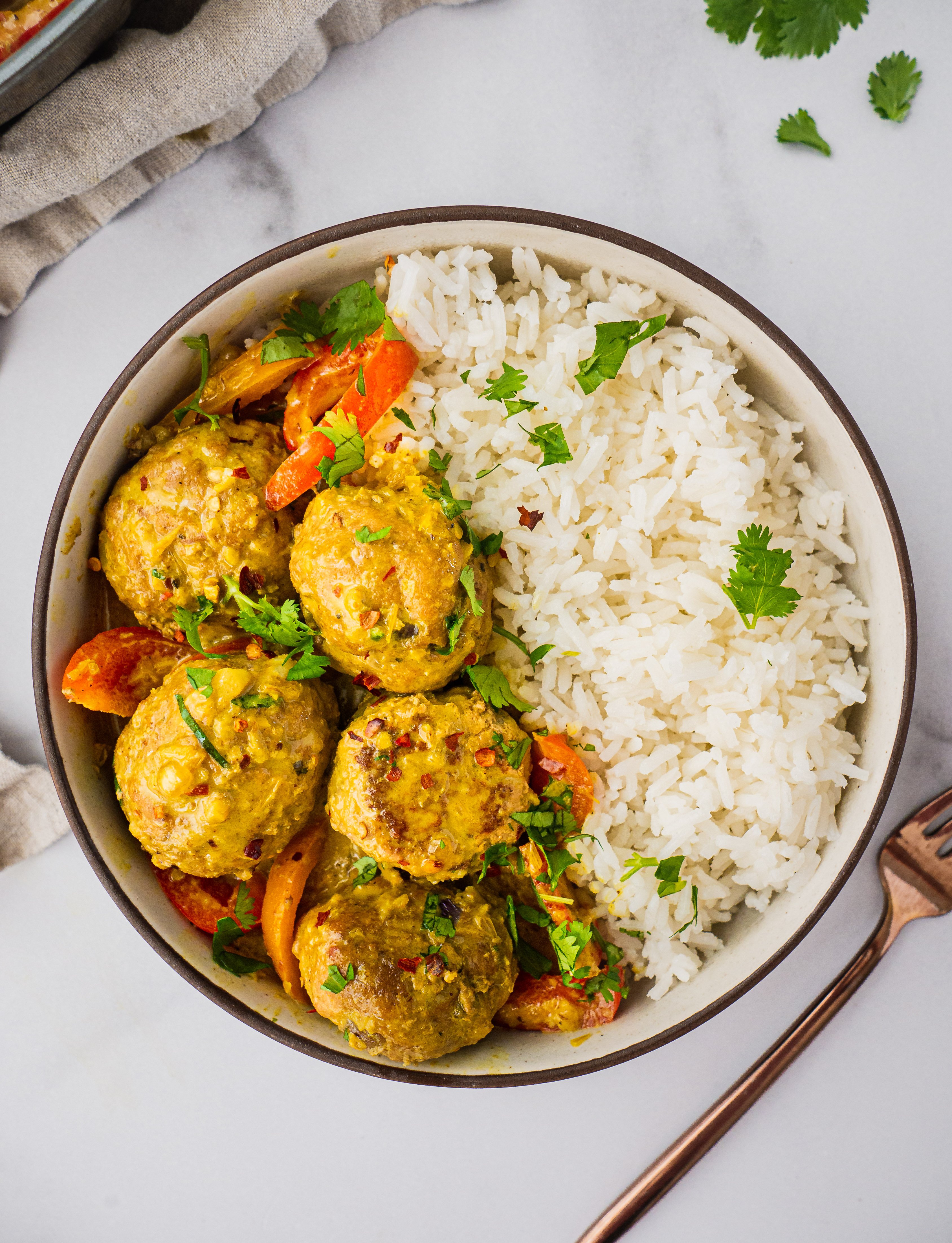 A bowl of jasmine rice and coconut curry meatballs with a sprinkle of cilantro on top.