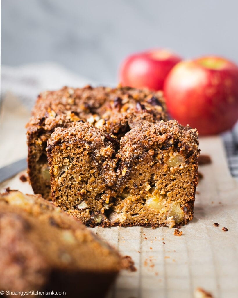 A loaf of sliced paleo apple cinnamon bread. There are some apple chunks in the middle of the sliced apple bread. This easy apple recipe is perfect for the fall season.