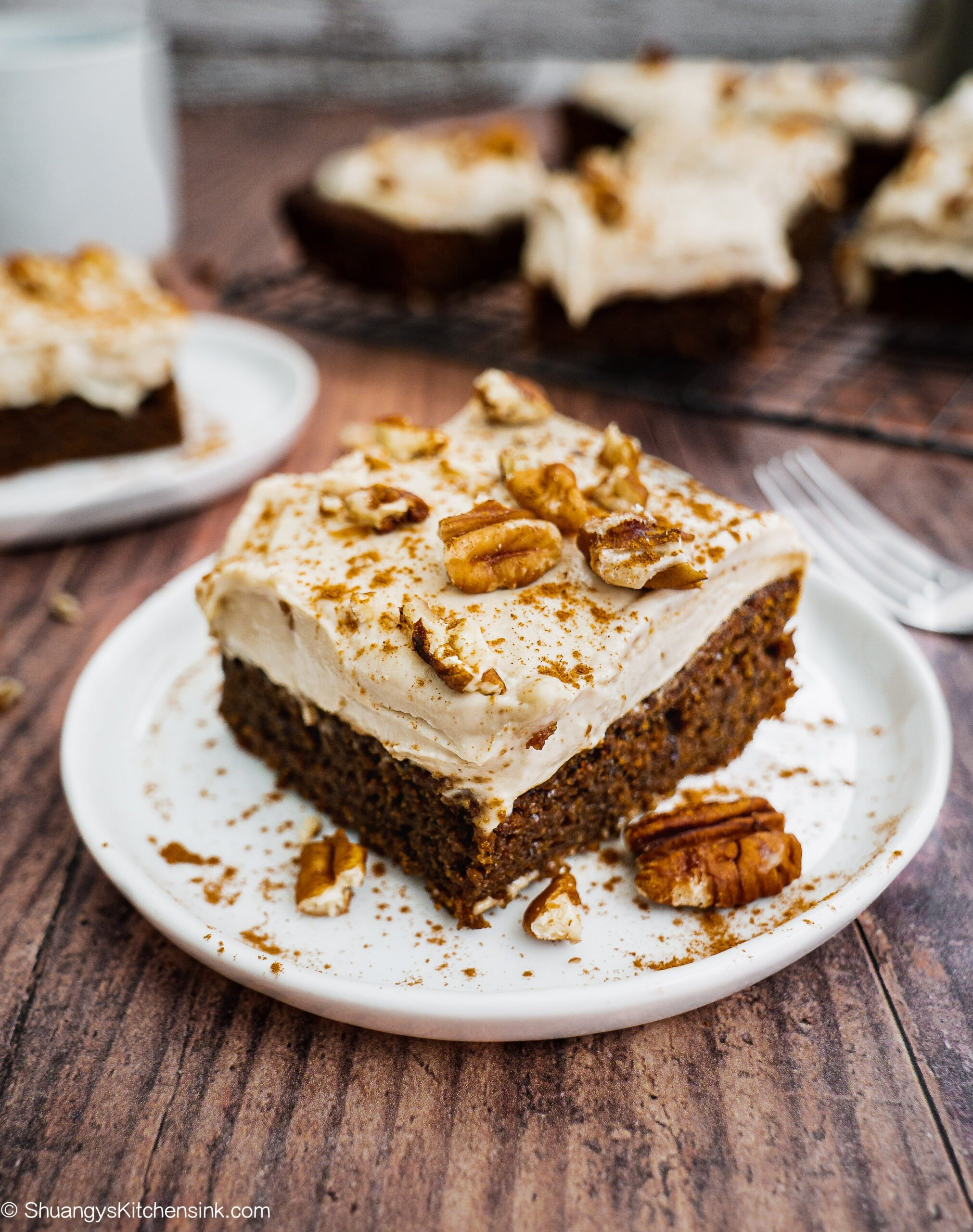 A piece of gingerbread cake with cashew cream frosting is on a wood board. There are some pecans and sprinkle of cinnamon on top.
