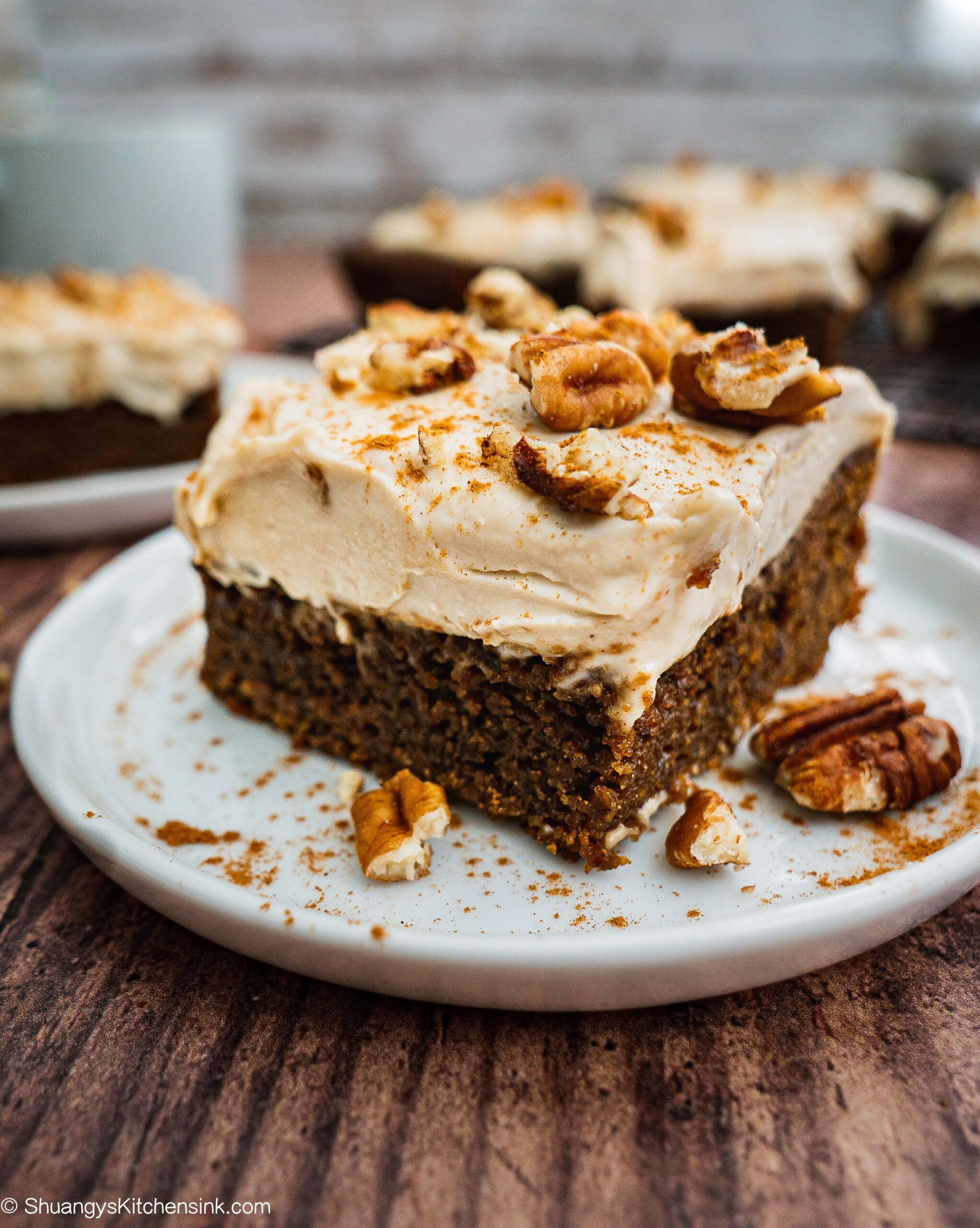A piece of vegan gingerbread cake with cashew cream frosting and crumbled pecans on top. There are more gingerbread cake in the background.