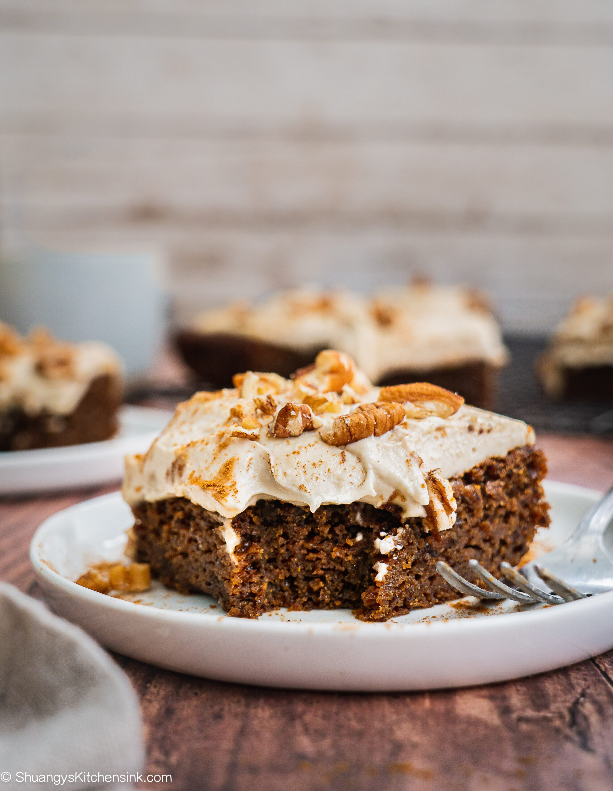 A piece of vegan gingerbread cake with cashew cream frosting and crumbled pecans on top. There is bite in the middle and a fork on the side. There are more gingerbread cake in the background.