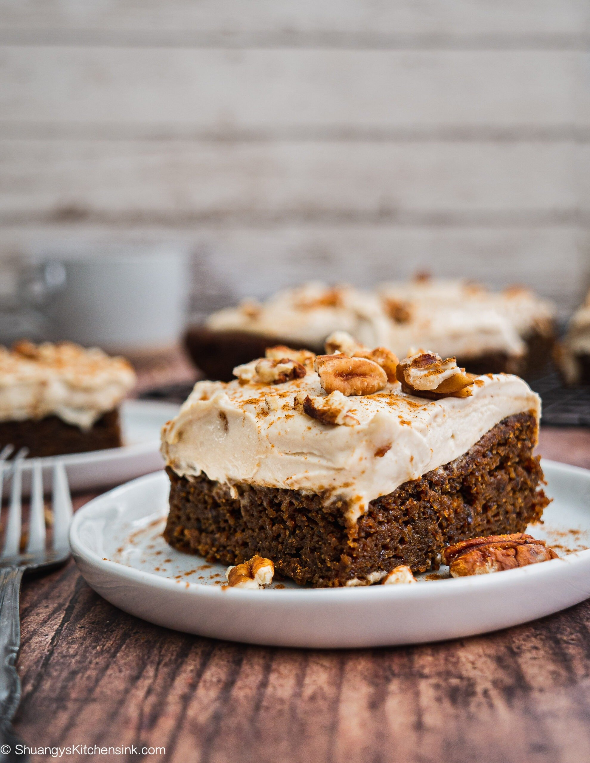 A piece of Vegan Gingerbread Cake with Cashew cream cheese with a sprinkle of pecans and cinnamon on top.
