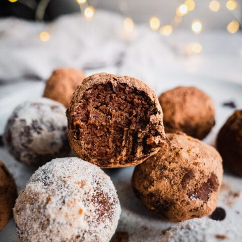 A gingerbread chocolate truffle ball with a bite on it. There are some that are coated with coconut flour, some are coated with cacao powder.