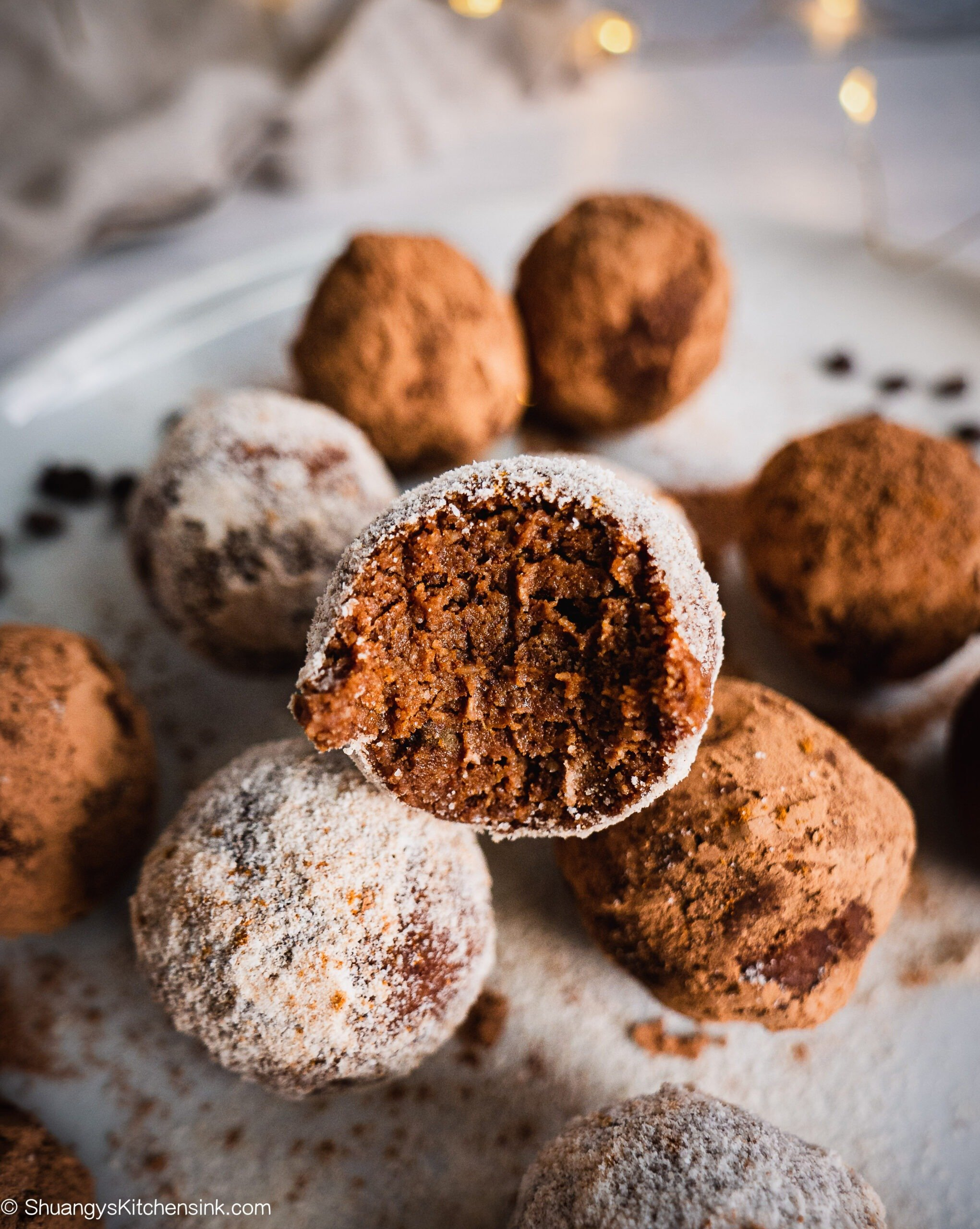 There is a bite on the gingerbread chocolate truffle balls. there are christmas lights in the back.