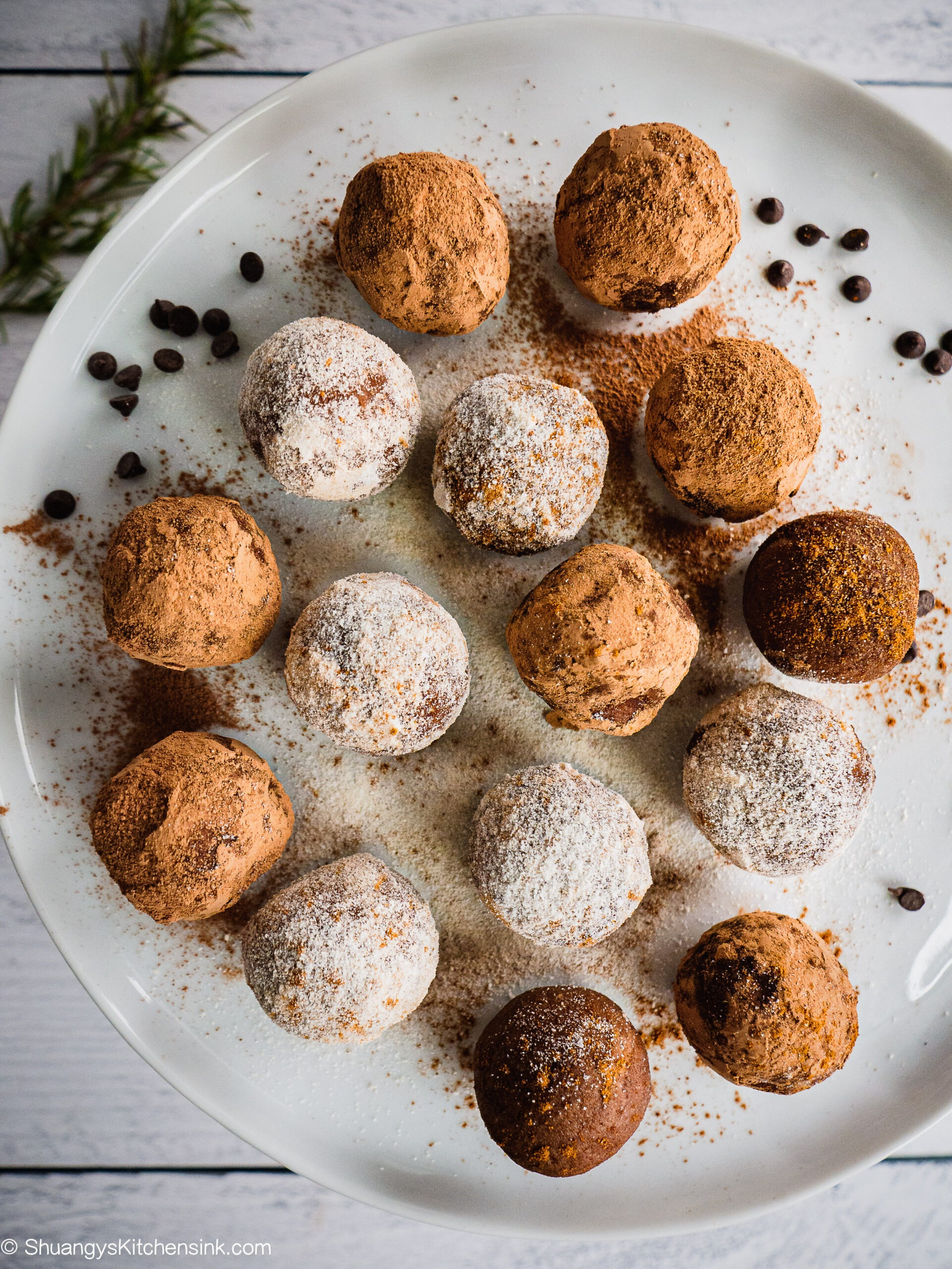 A plate of gingerbread chocolate truffles. Some are covered with coconut flour some are covered with cacao powder. There are christmas lights in the background.