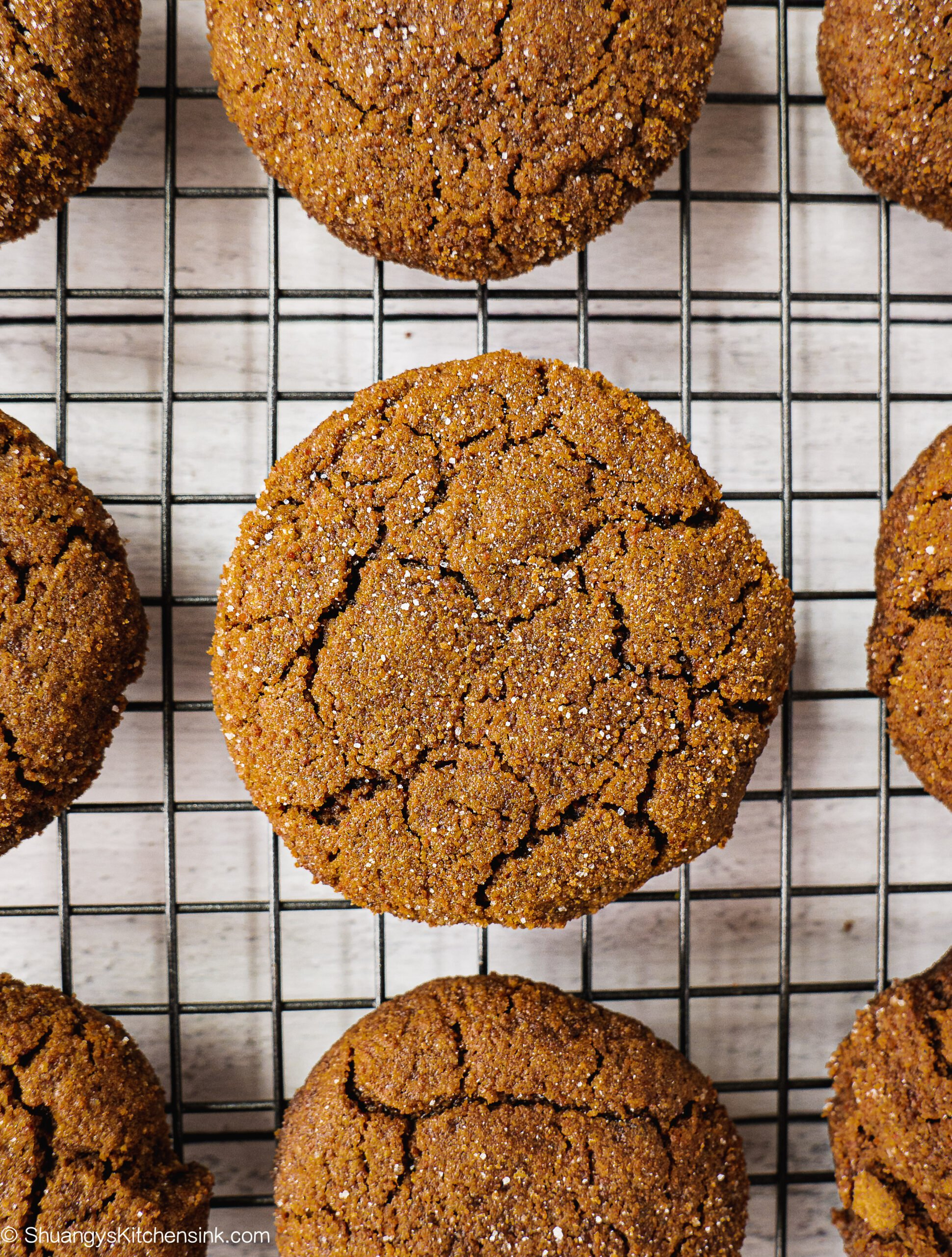Baked gingerbread cookies cooling on a wire cooling wrack. There is crack on the cookies.