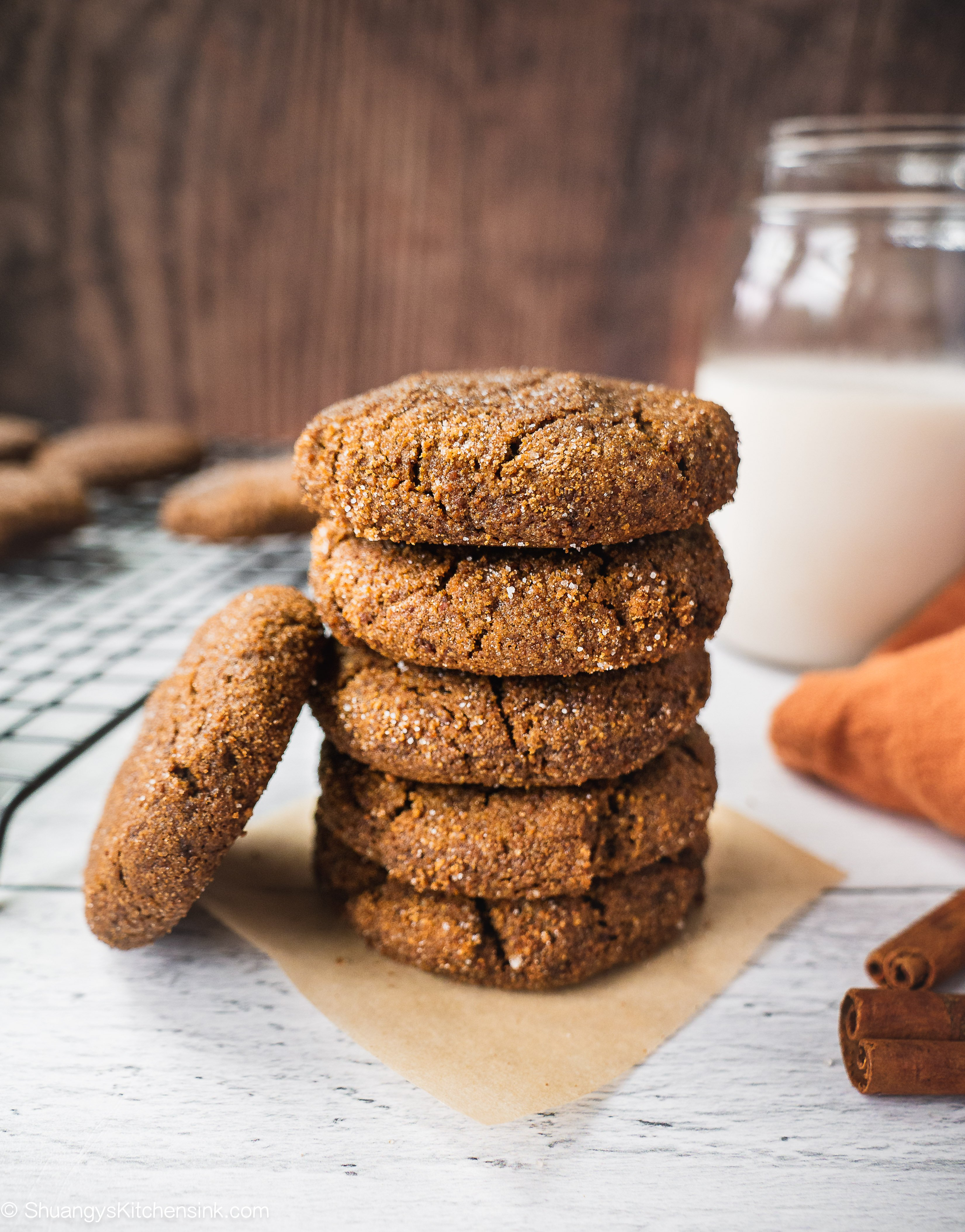 A stack of paleo ginger bread cookies with a glass of milk and cinnamon sticks in the background. There is a cookie leaning on the cookie stack.