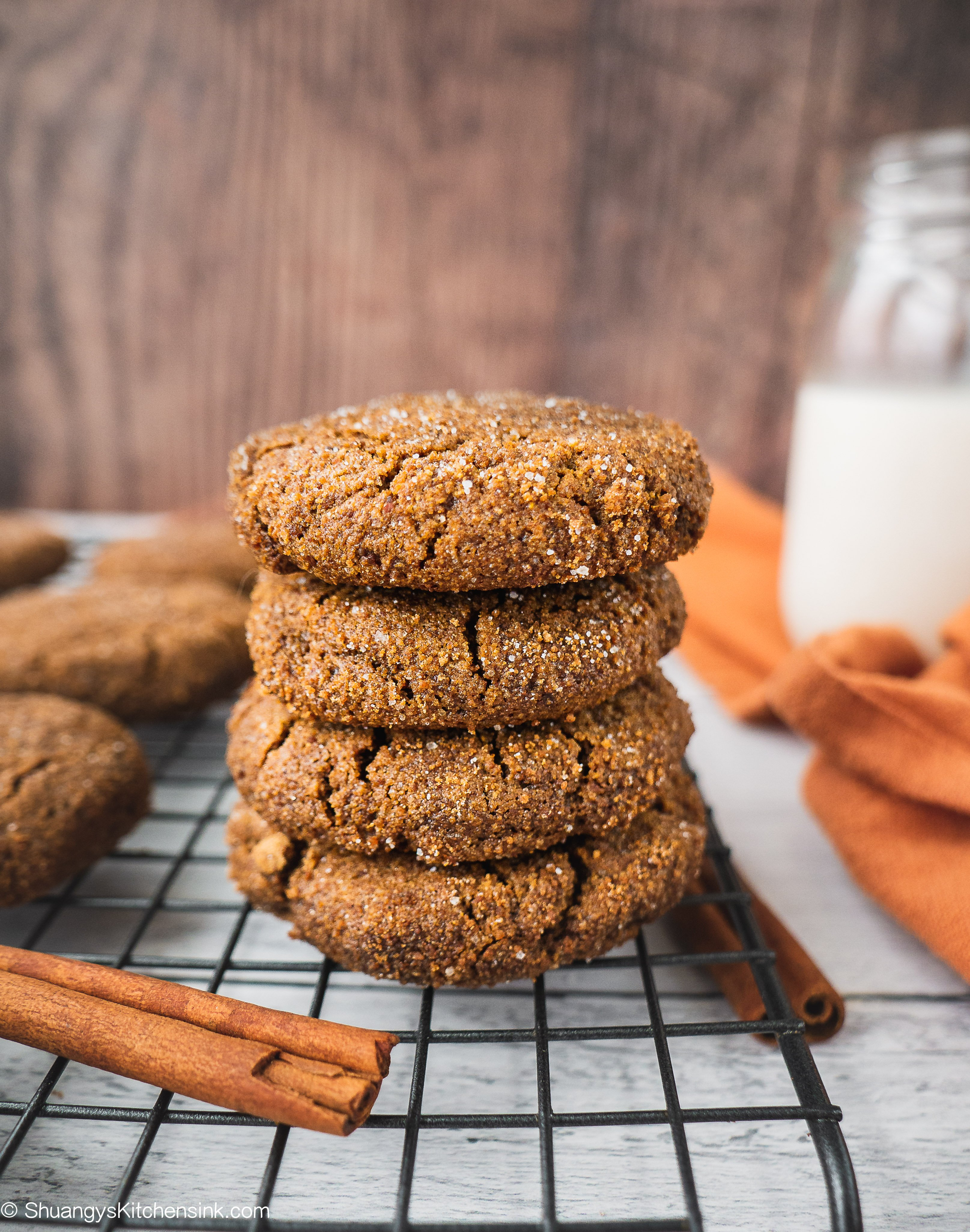 A stack of paleo ginger bread cookies with a glass of milk and cinnamon sticks in the background.