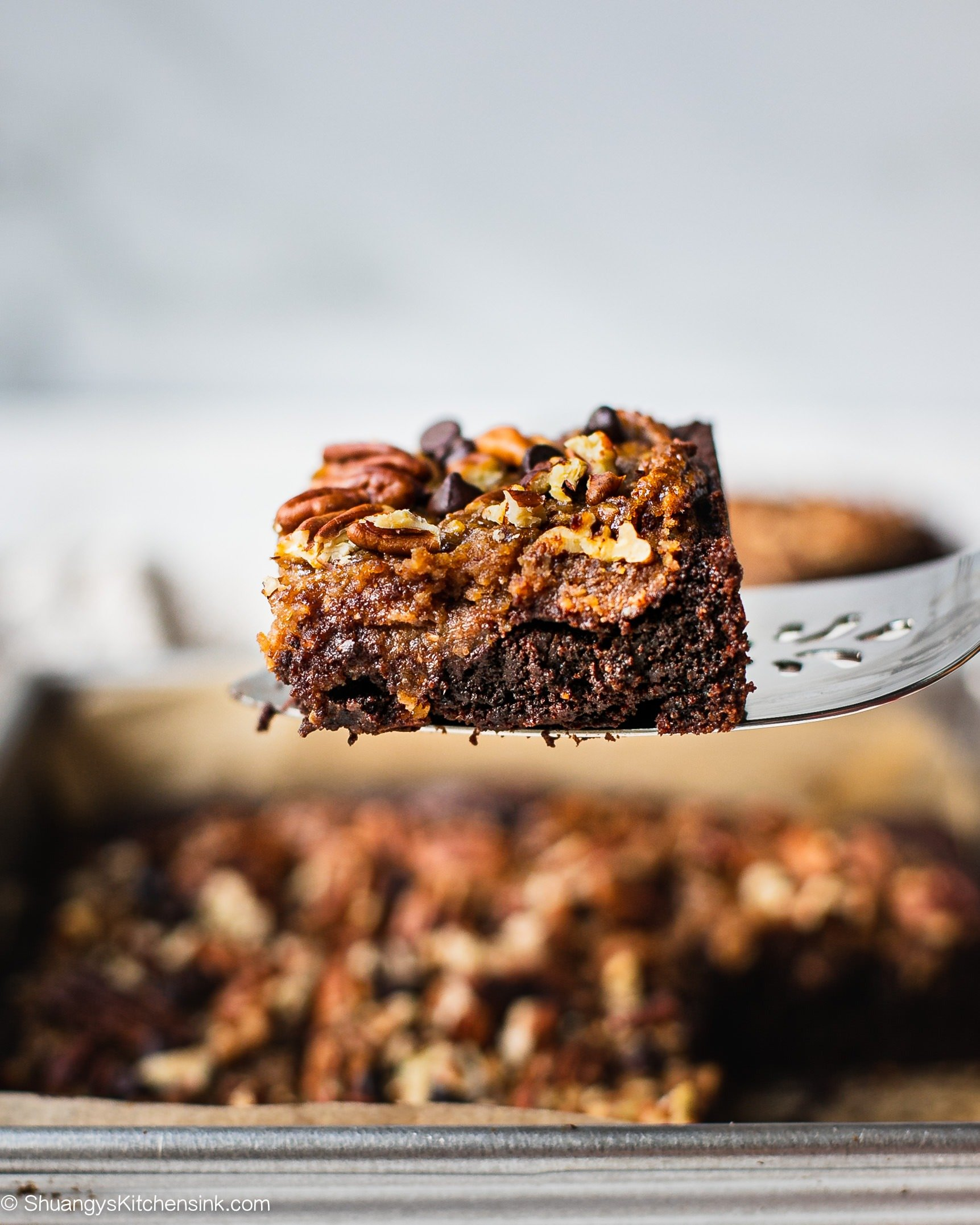 A piece of caramel pecan brownie with healthy almond flour brownie topped with gluten free pecan pie.