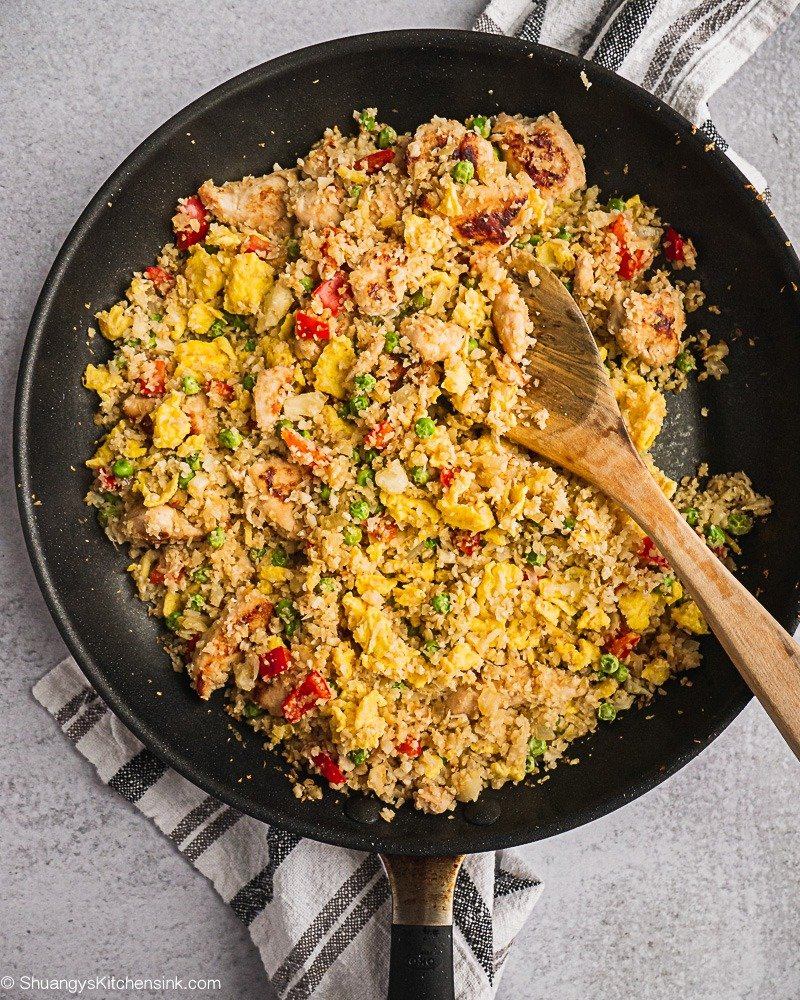 A pan of cauliflower fried rice with chicken that is colorful and so flavorful.