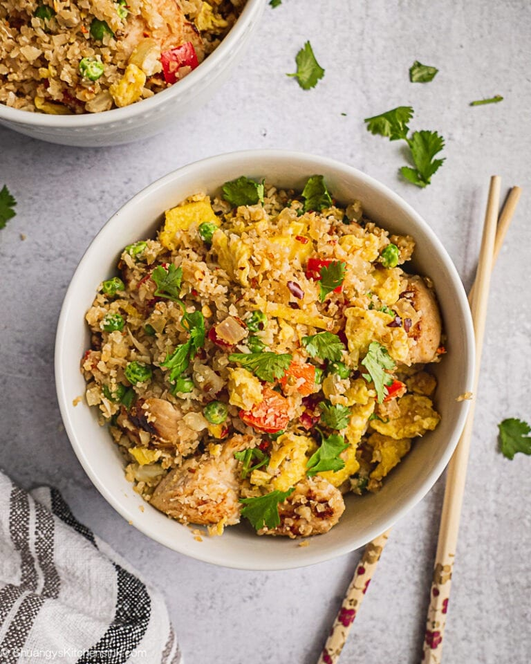 A bowl of cauliflower fried rice with chicken that is colorful and so flavorful. There is a pair of chopsticks and some fresh cilantro on the table.