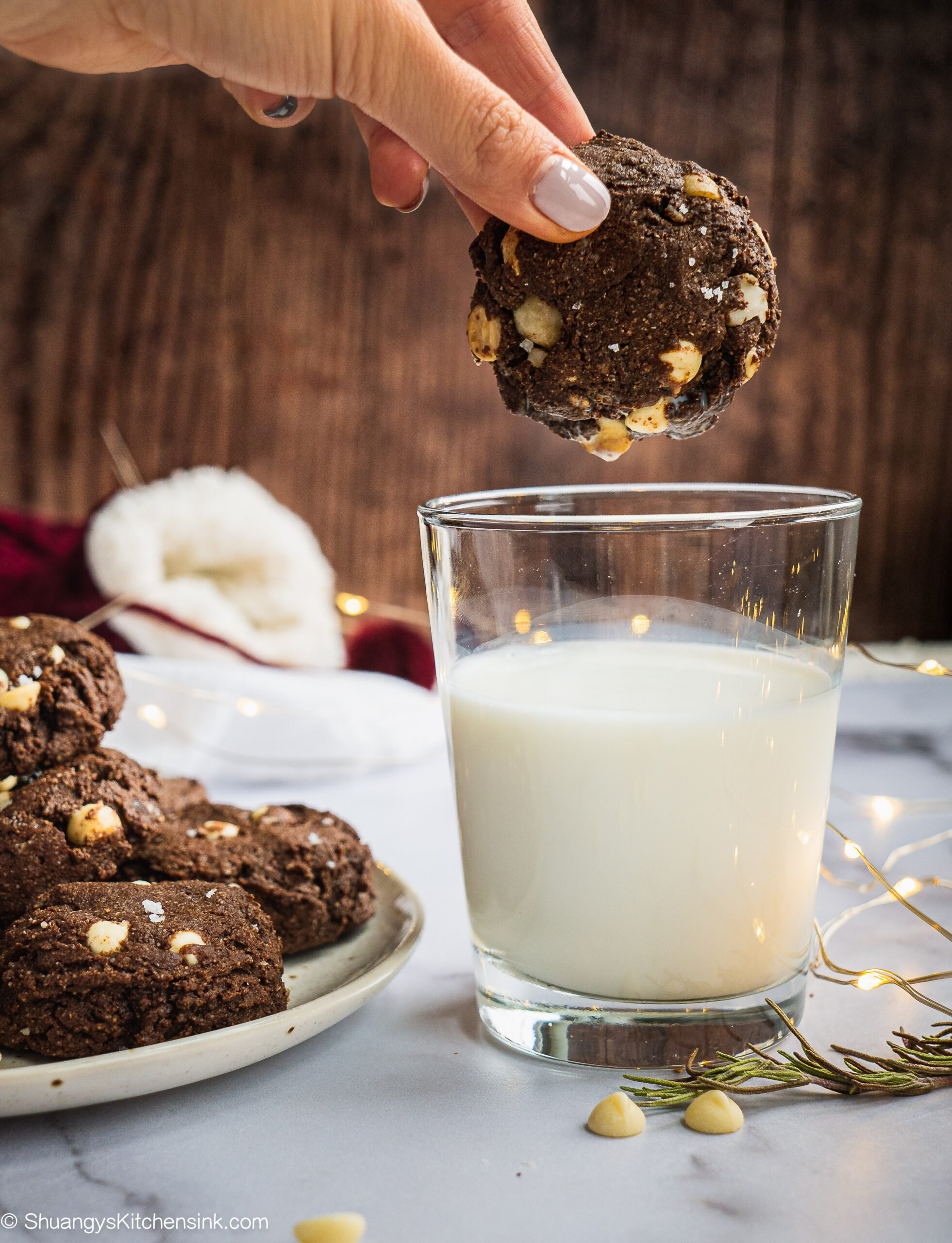 A Plate of White Chocolate Macadamia Nut cookies with a glass of milk in the background. One of them has a bite in it. There are Christmas lights in the background. A hand is grabbing a cookie to dip in the milk.
