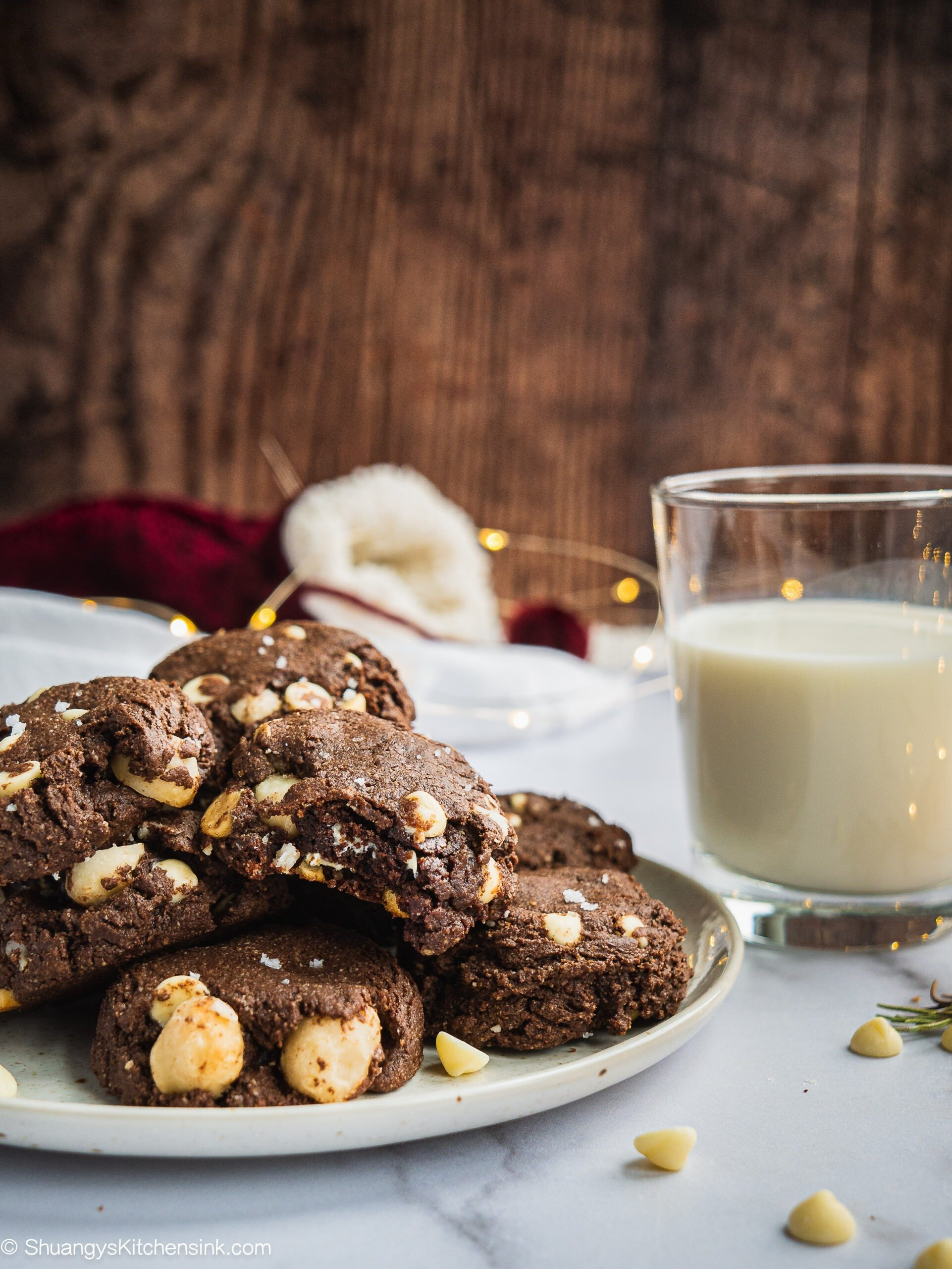 A Plate of White Chocolate Macadamia Nut cookies with a glass of milk in the background. One of them has a bite in it. There are Christmas lights in the background.