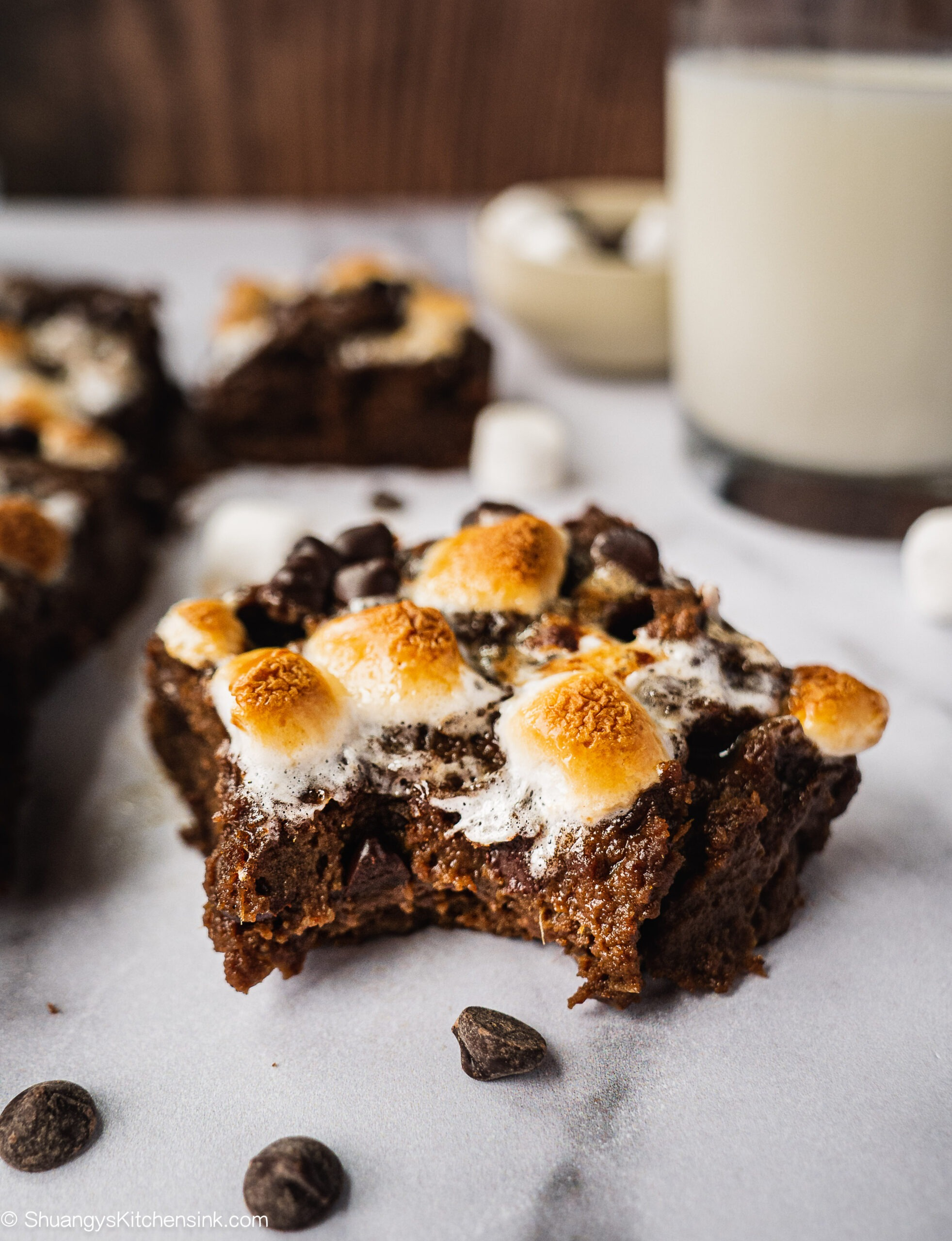 A piece of hot chocolate brownie topped with caramelized marshmallows. There is a glass of milk in the background.