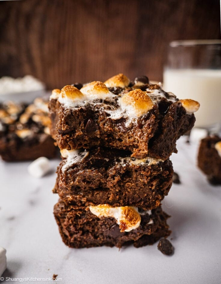 A stack of hot chocolate marshmallow sweet potato brownies. The top has a bite. The texture appears to be gooey and moist.