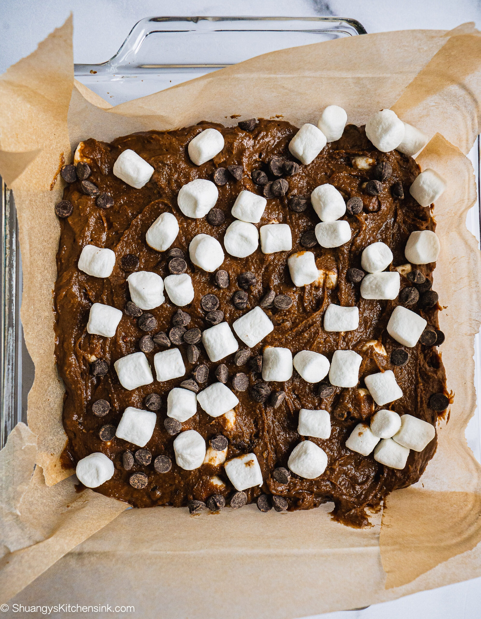 A pan of raw sweet potato brownie batter in a parchment paper lined baking dish. There are marshmallows and chocolate chips on top.