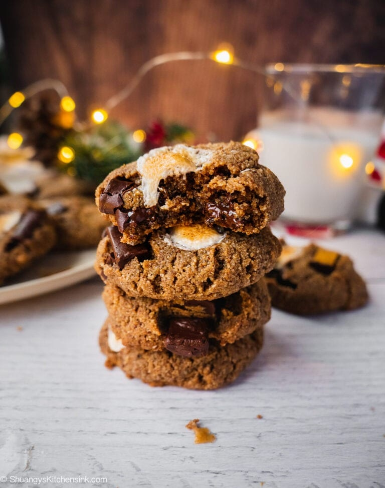 A stack of chocolate chip smores cookies. The top cookie has a bite in it. There are Christmas lights, and a glass of milk in the background.