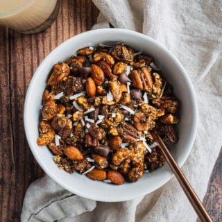 A bowl of paleo, vegan and low sugar gingerbread granola with a glass of milk in the bakcground.