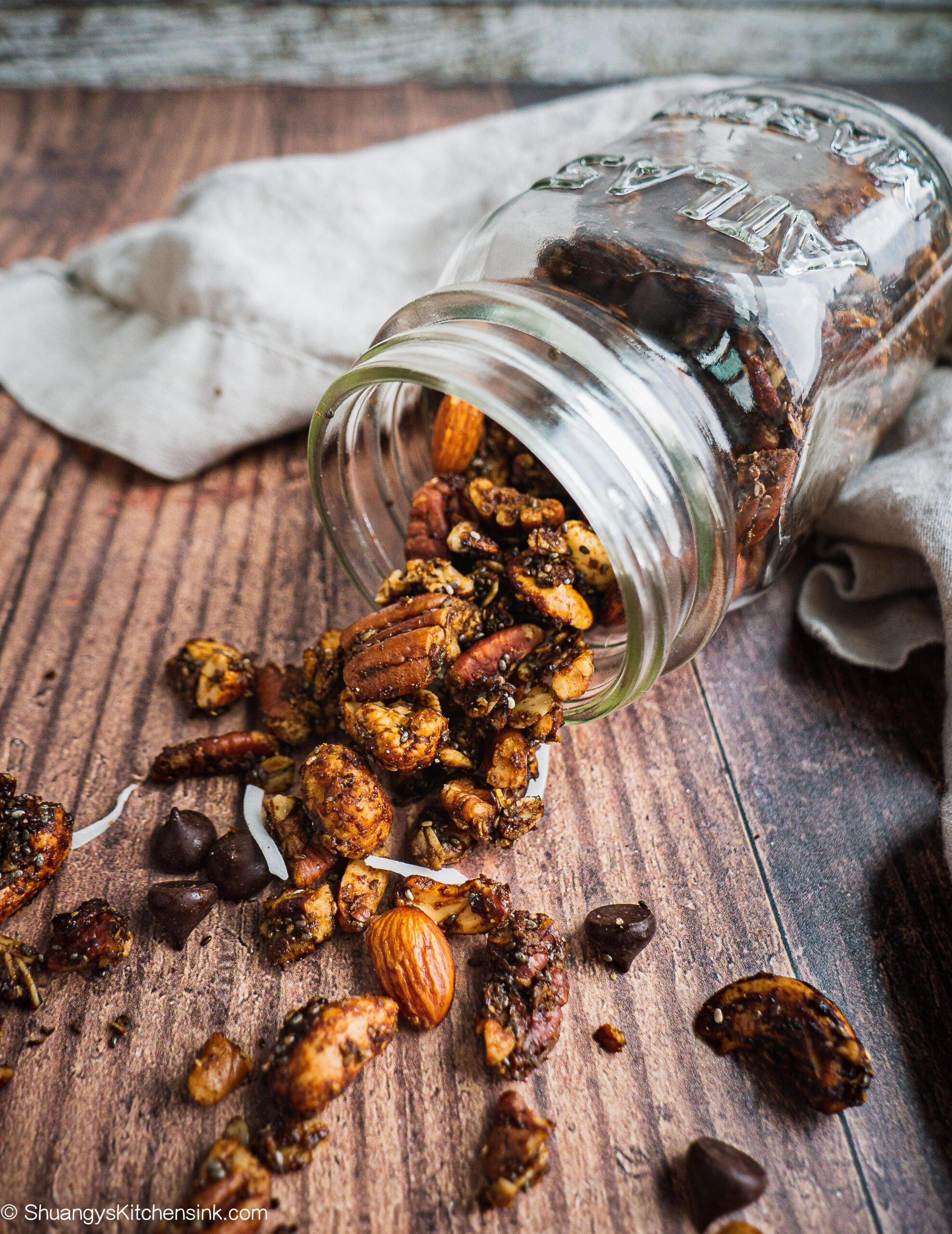 Healthy vegan nut granola spiced with gingerbread spices are coming out from a mason jar that's laying down on a wooden table. there are some shaved coconut and chocolate chips in the table as well.