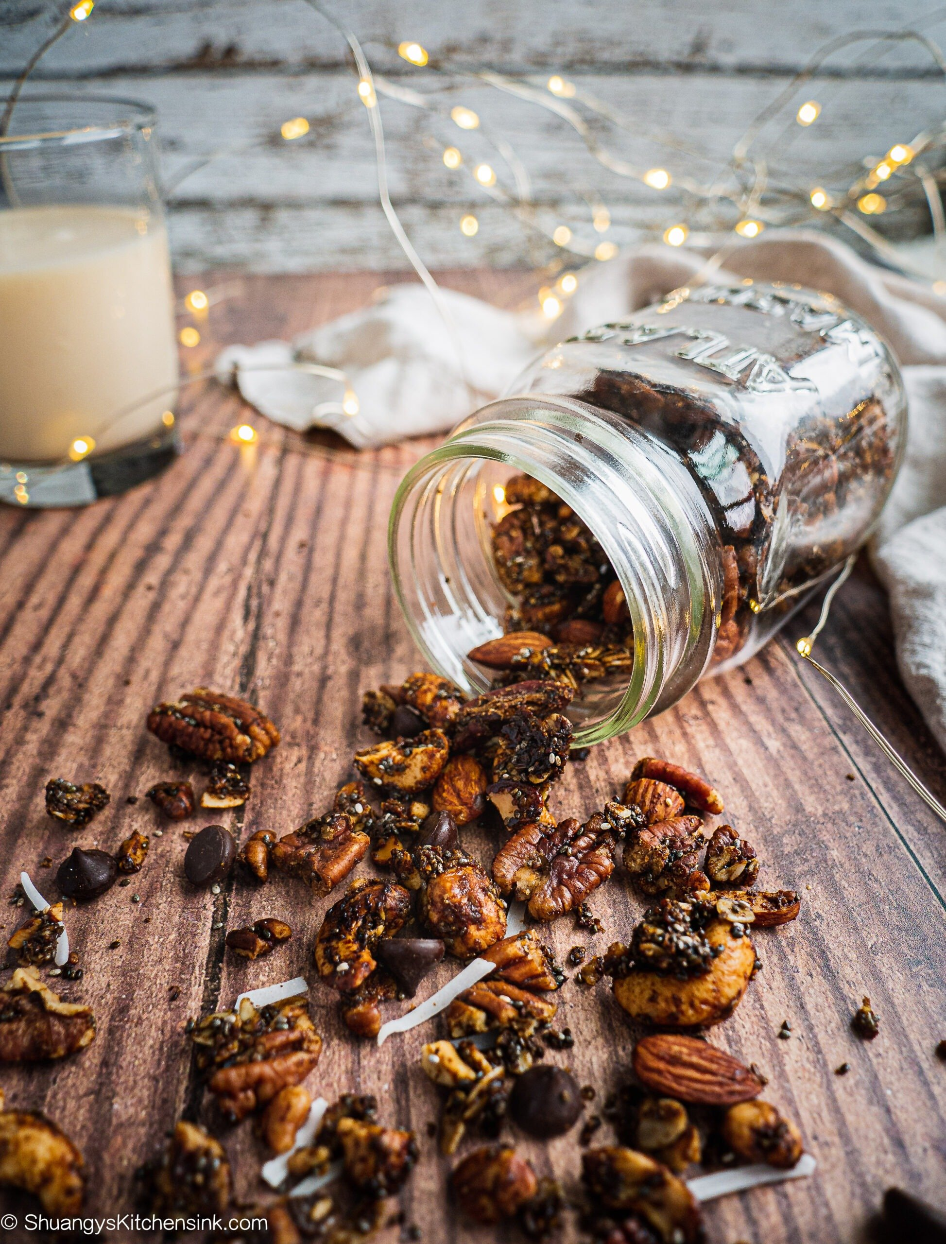 A jar of healthy Christmas Gingerbread Granola spilt on a piece of wood slap. There is a glass of milk and christmas lights in the background.