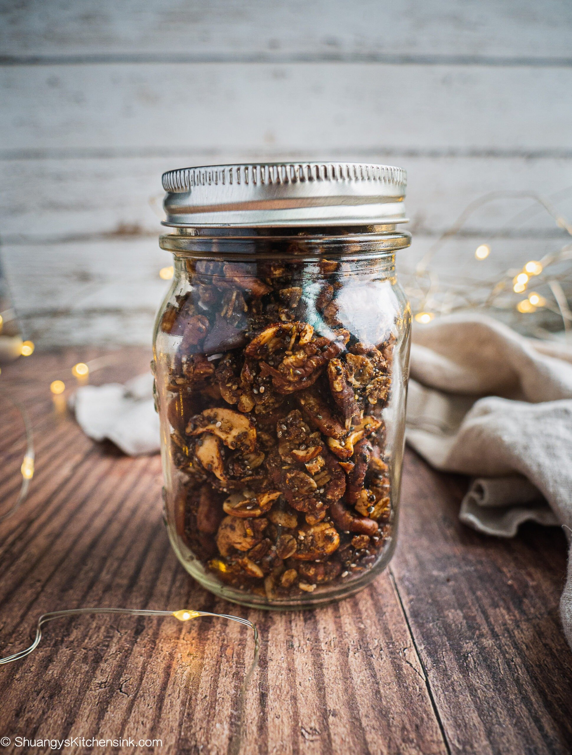 The picture shows how you can store the nut based  paleo gingerbread granola in a mason jar with an air-tight cap. There is Christmas lights in the background.