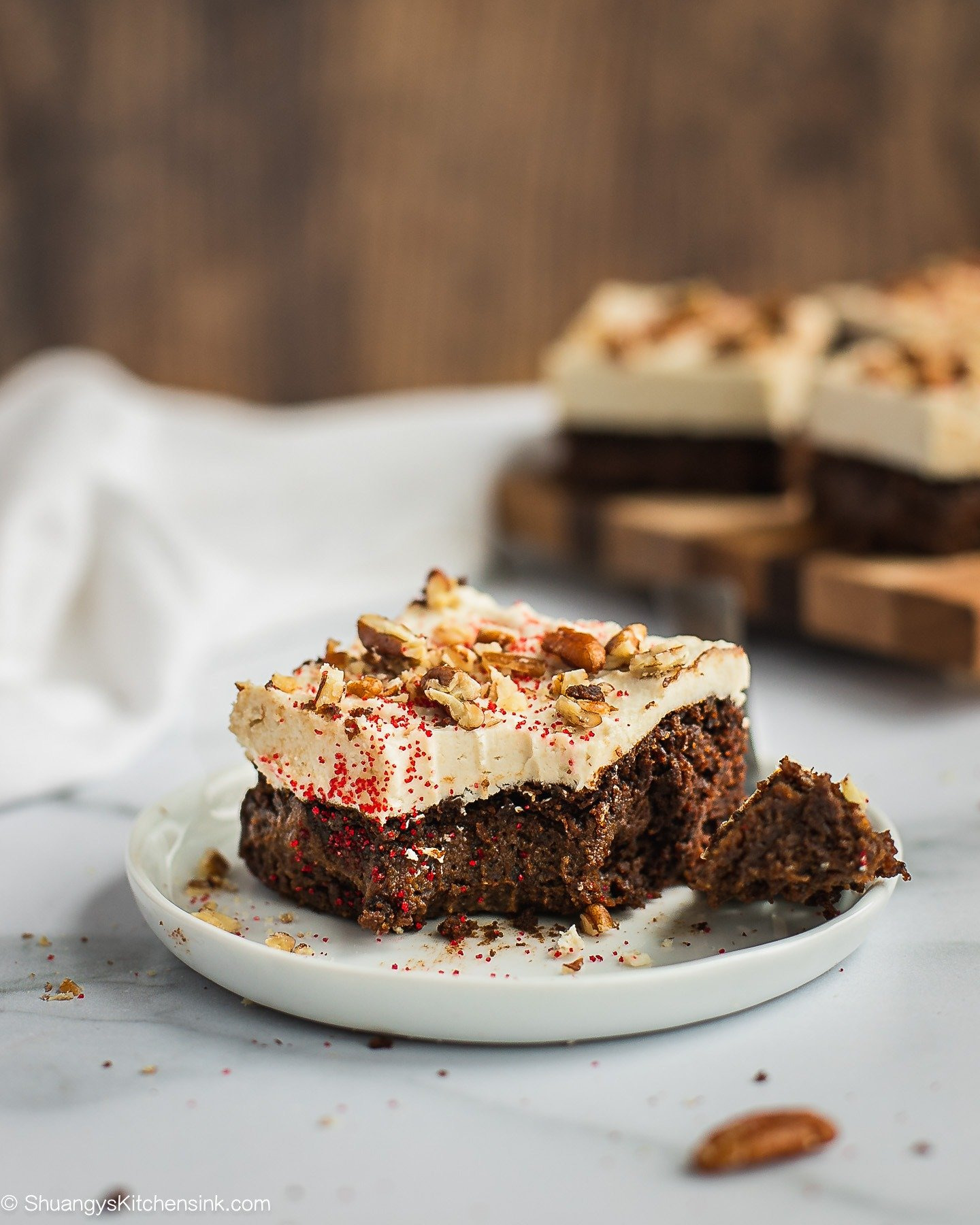 A piece of chocolate cake with cream cheese frosting with a bite in the middle. There are pecans on top.