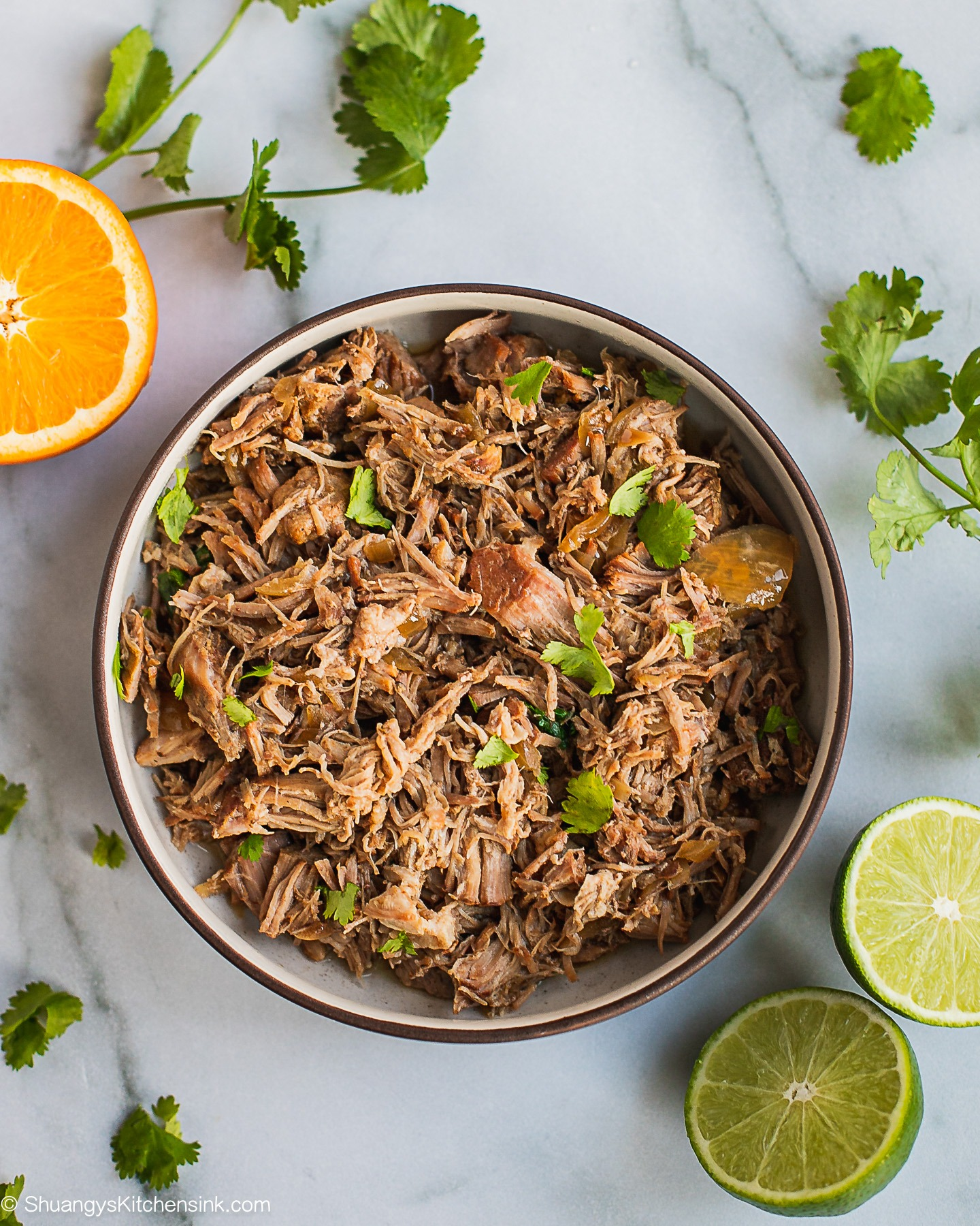 There is a bowl of pulled pork topped with cilantro. There are lime and orange halfs on the table as well.