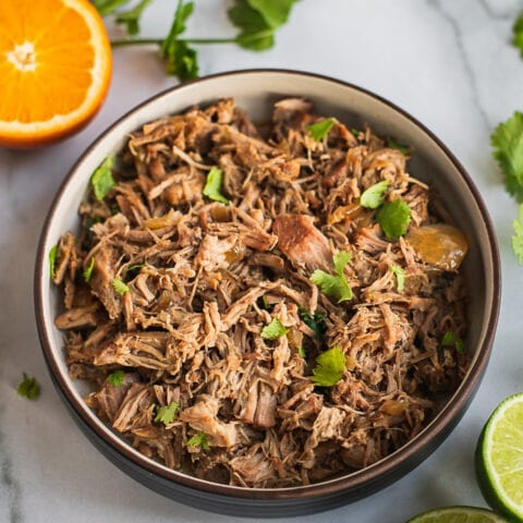 A bowl of pulled pork carnitas with a few pieces of cilantro on top. And there is half of a piece of orange in the back.